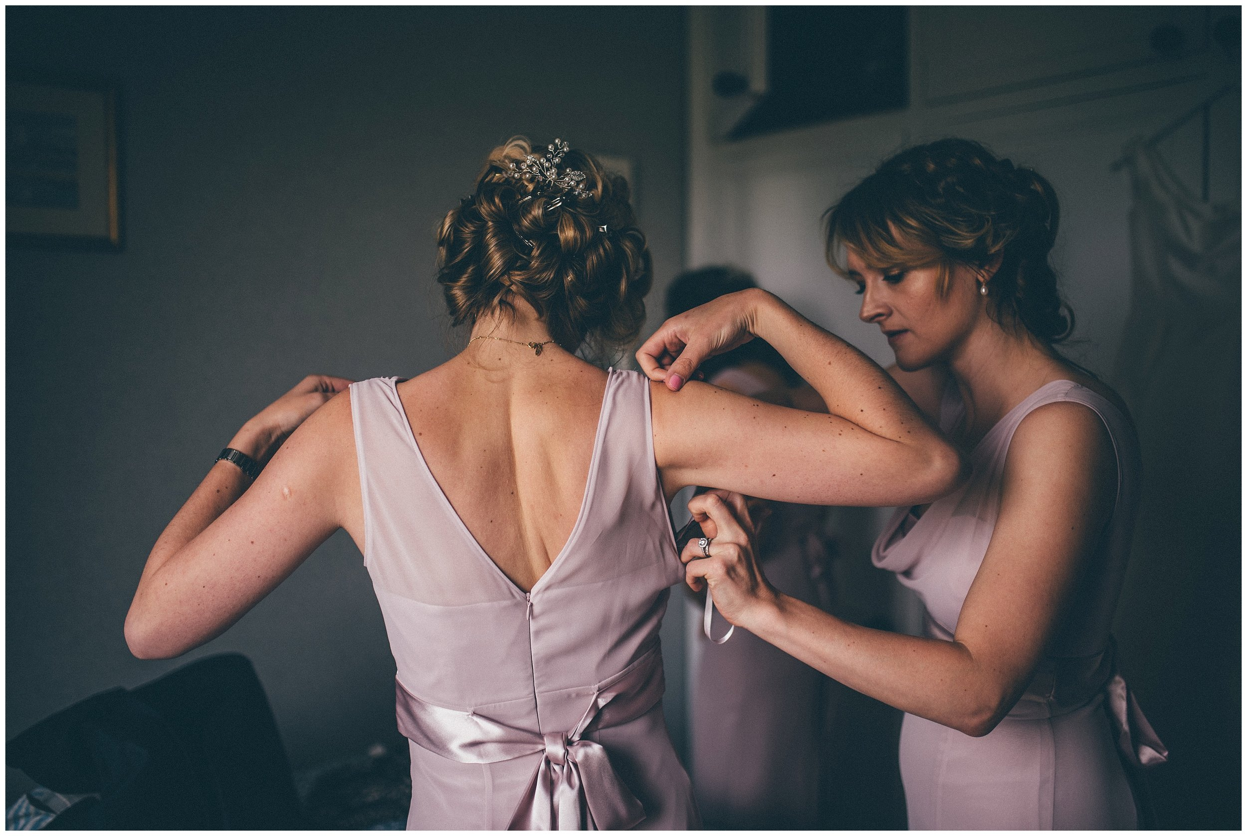 bridesmaids help each other into their dresses.
