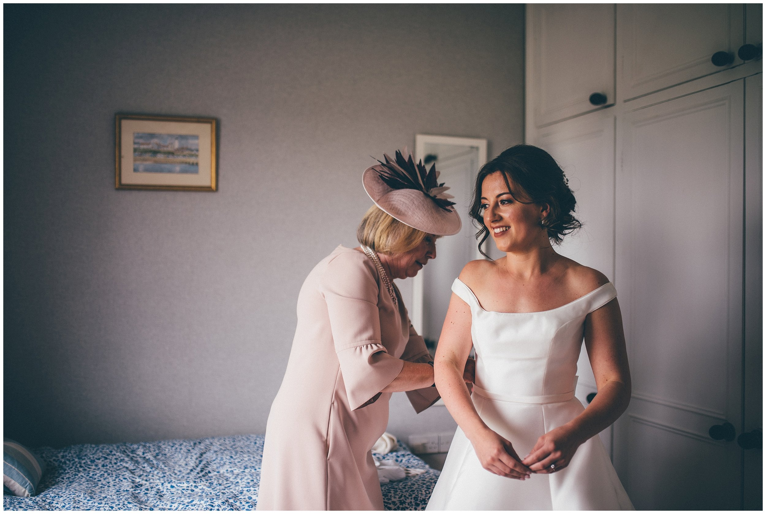 Bride gets helped into her wedding dress by her mum.