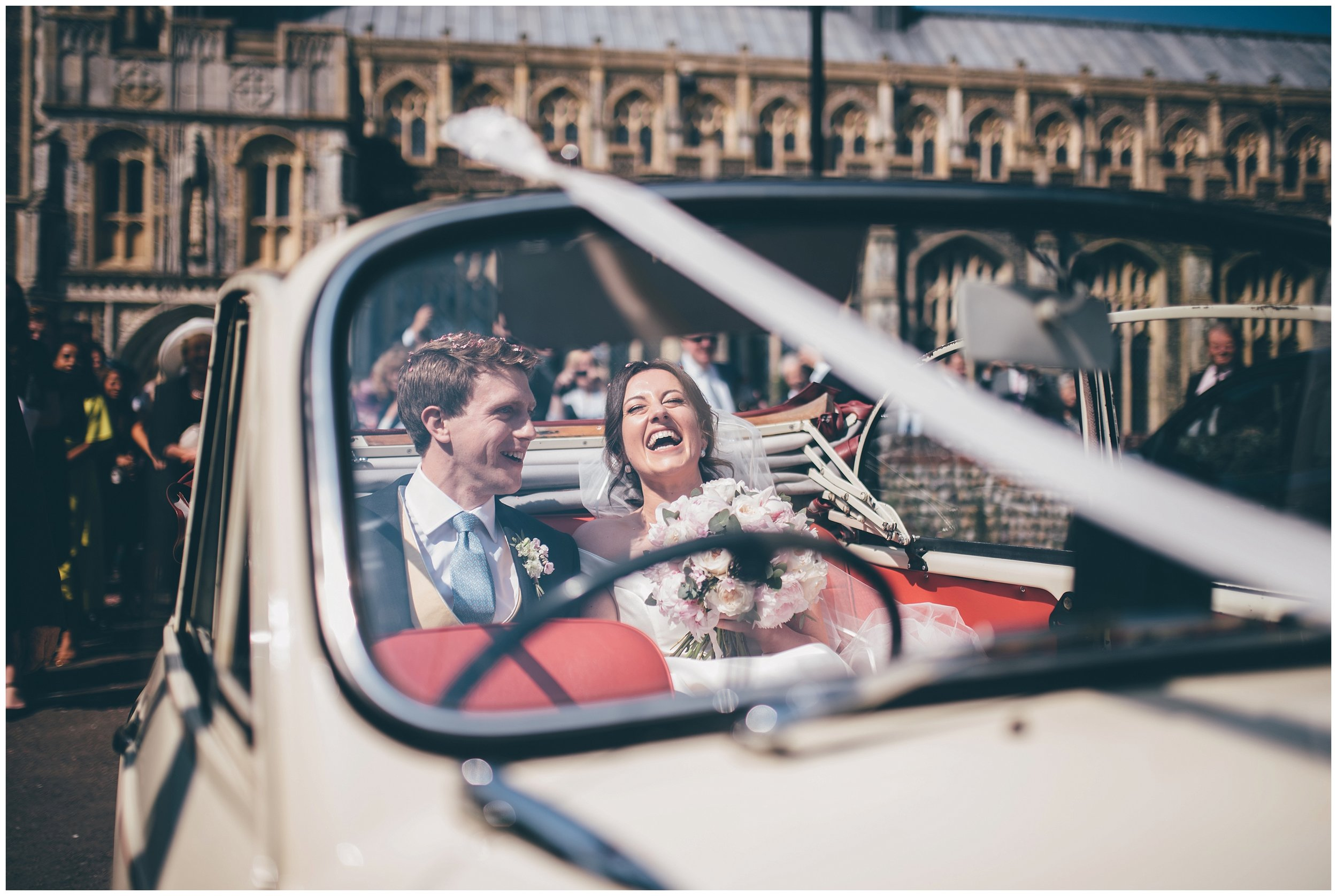 Bride and groom leave their wedding in their old classic car for their wedding reception.