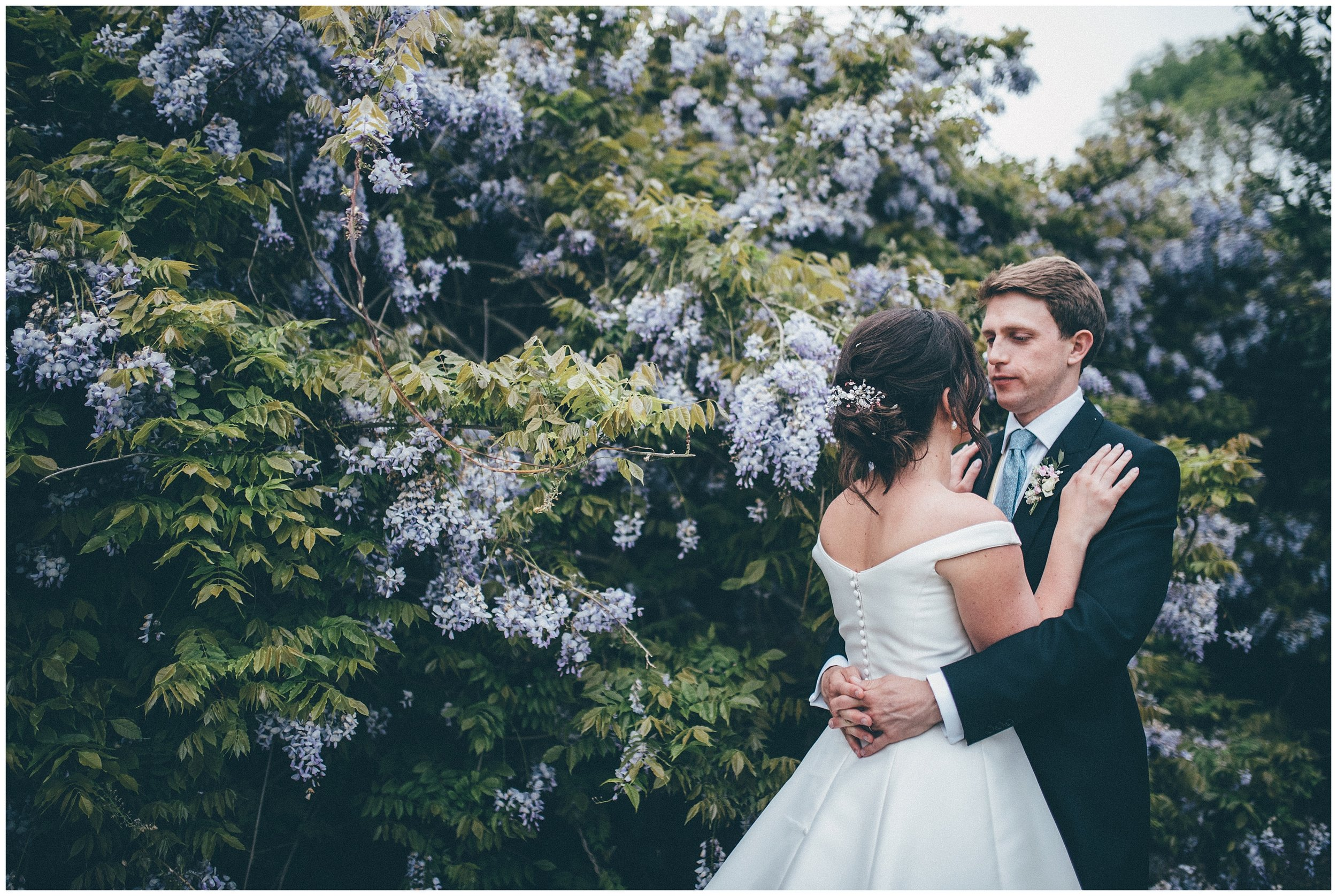 Bride and groom in front of beautiful flowers on their wedding day at Henham Park.