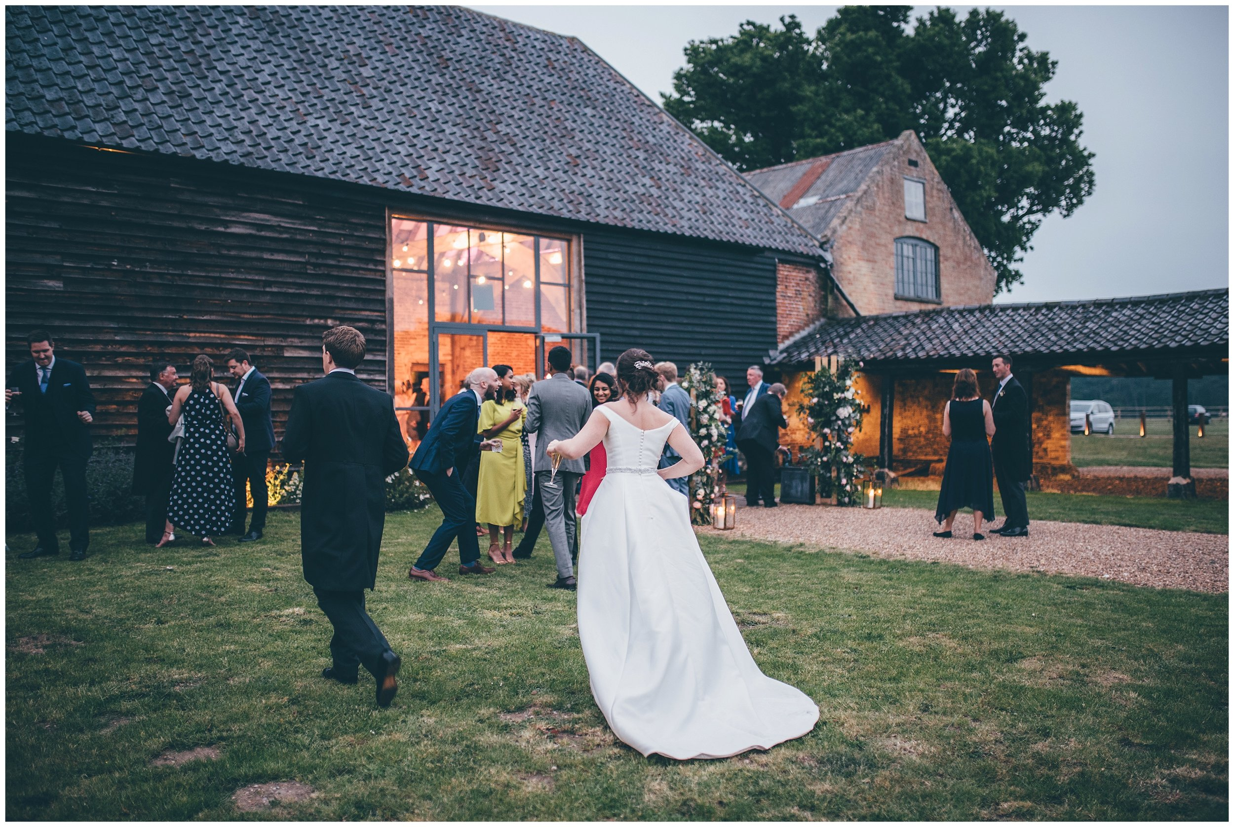 Bride and groom greet their evening guests at Henham Park wedding barns..