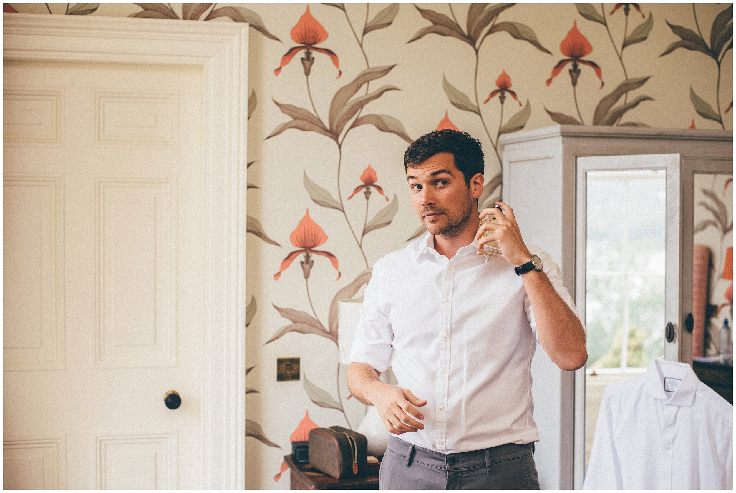 Groom sprays his aftershave ahead of his wedding at Silverholme Manor.