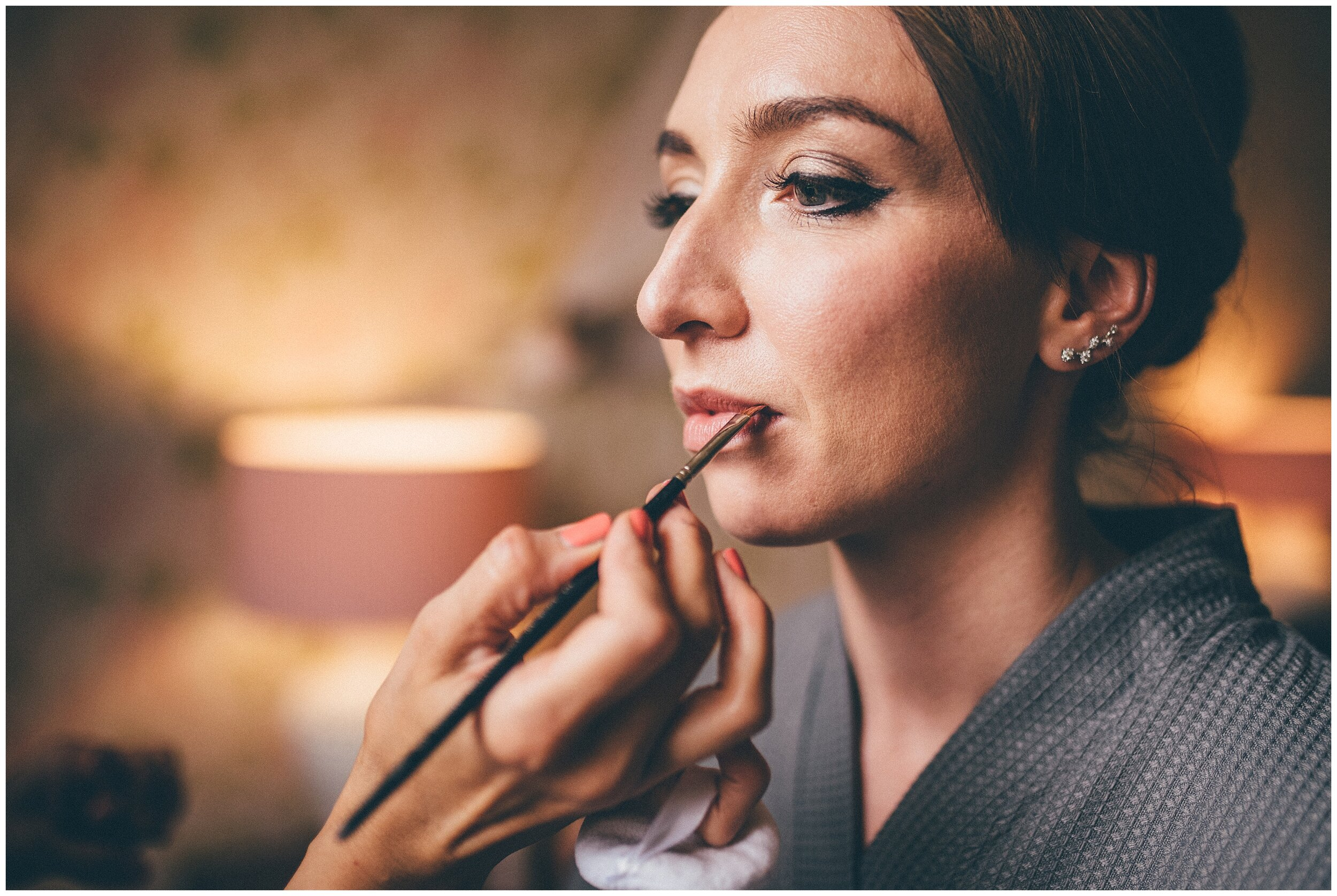 Bride gets her finishing touches done on her make-up before her Lake District wedding.