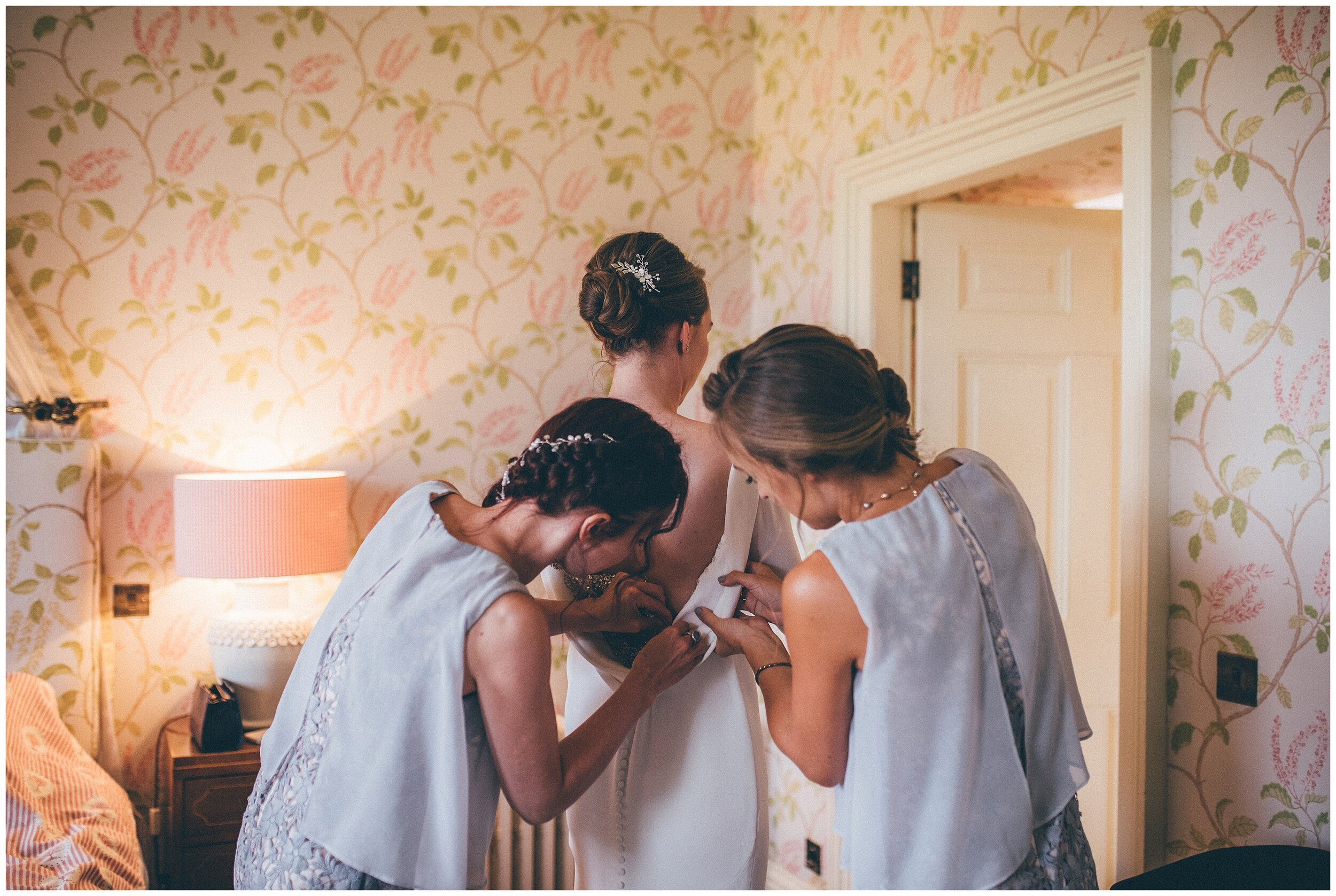 Bridesmaids wearing grey bridesmaid dresses help the bride into her Pronovias gown.