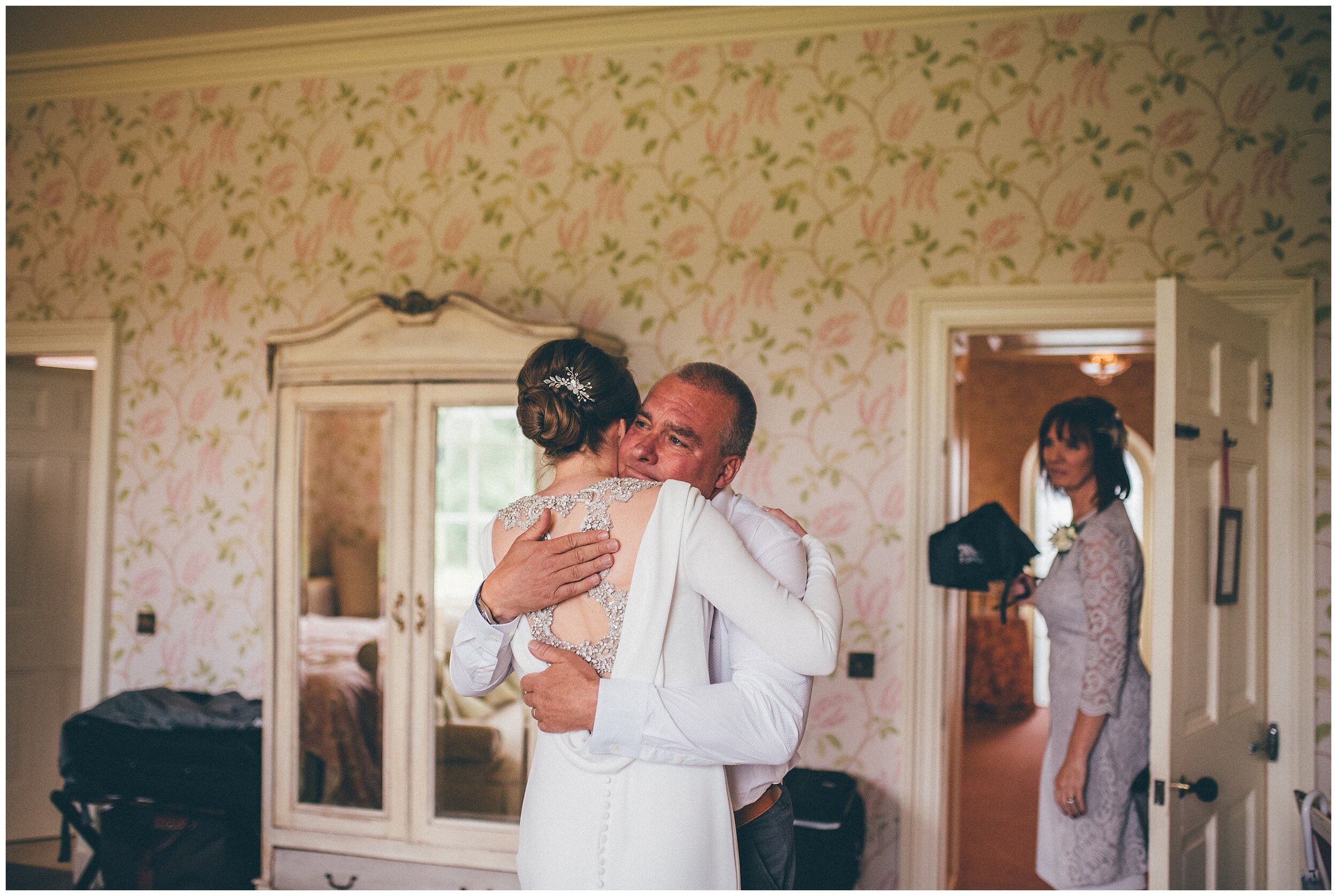 Bride's dad hugs her as he sees her as a bride for the first time.