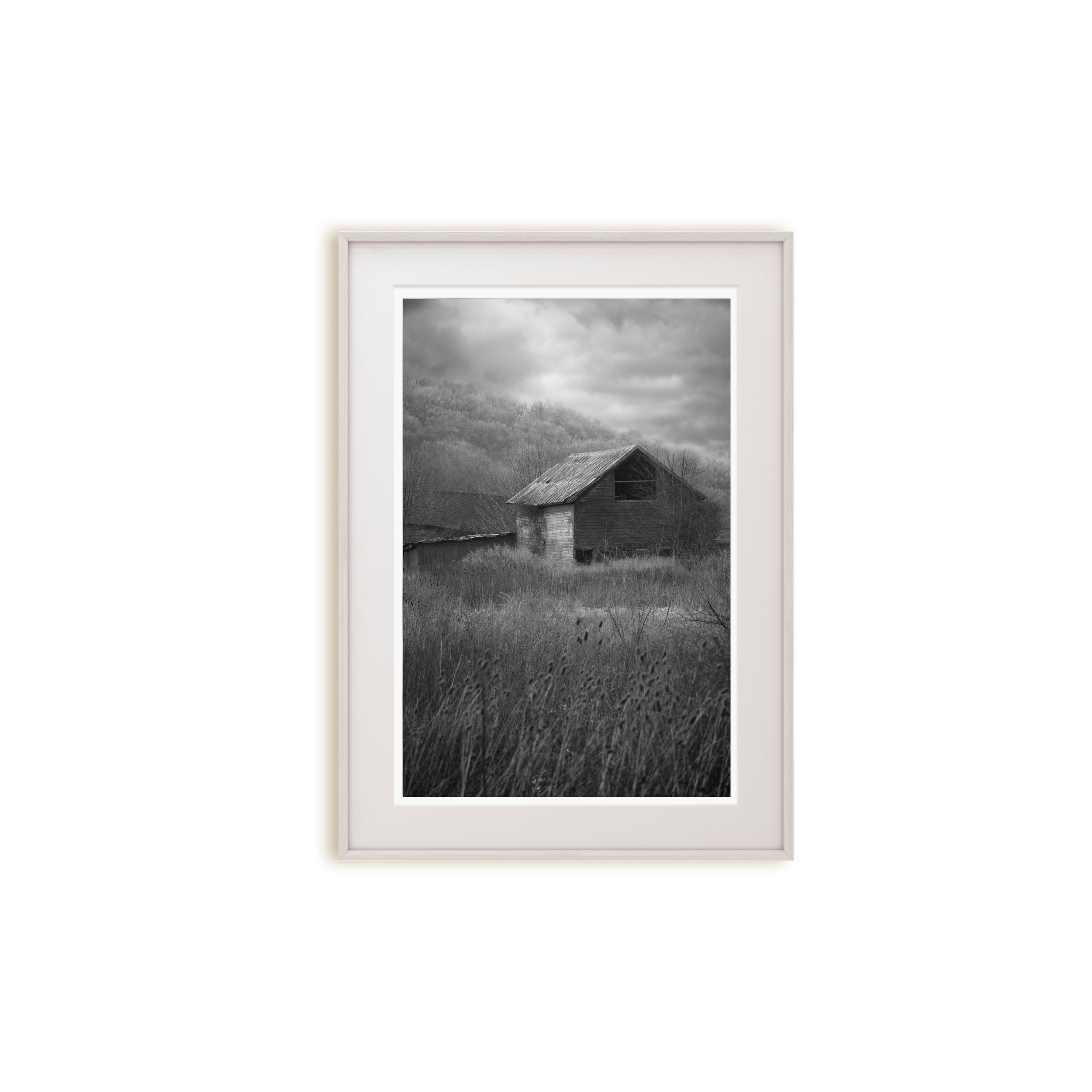 A moody black and white print of an abandoned building