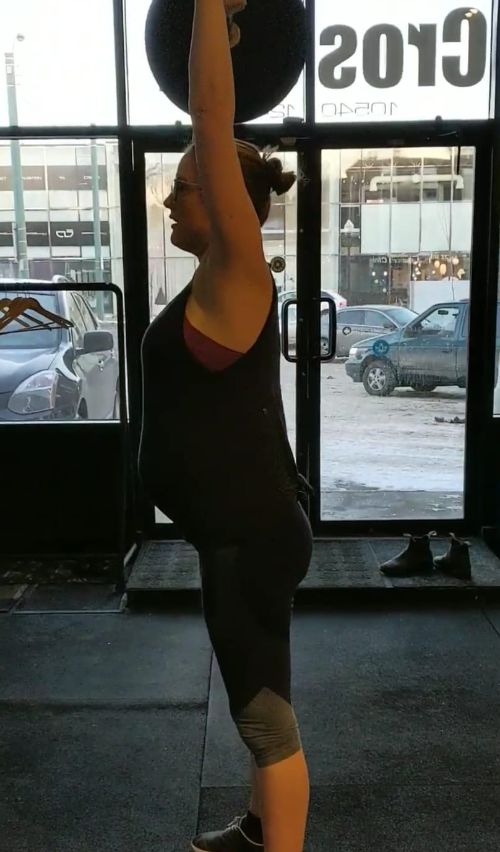 Carolyn, performing thrusters at 8 months pregnant.