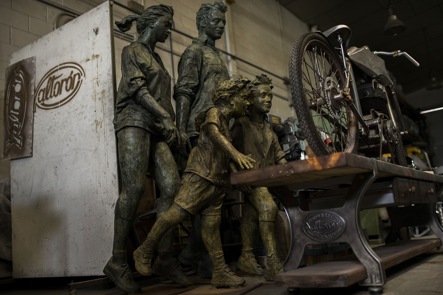 "Bronze sculptures  are displayed behind "" Gutdman "", and unfinished 235cc  Mv Deva Agusta   motorbike   customization  at Valtorón's workshop garage on July 21, 2014 in Valdetorres del Jarama, Spain. Brothers Carlos and Pablo Delgado are cast sculptors who invest part of their time as  Valtorón Sculptured Motorcycles . On their foundry they desing and bring to life motorbike's bodyworks and tanks handmade by steel pieces recycled from scrapped  motorcycles . Cast sculptors, a community trader and a musician have something in common: they have made the passion of customizing motorbikes their own business. Valtoron Sculptured Motorcycles, Café Racer Obsession and El Solitario Motorcycles are the dreams-come-true of the Delgado Brothers, Federico Ruiz and David Borrás."