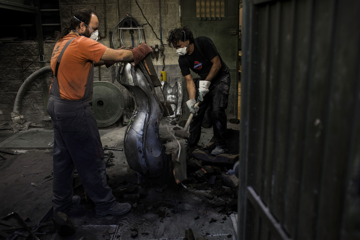Brothers  Carlos  (R) and  Pablo Delgado  (L) break the  silica-sand mould  that contains the  recycled steel bodywork  of a  customized BMW R Ninet   motorcycle  at Valtorón's  foundry  on July, 30, 2014 in Valdetorres del Jarama, Spain. Carlos and Pablo Delgado are  cast  sculptors who invest part of their time as  Valtorón Sculptured Motorcycles . On their foundry they desing and bring to life motorbike's bodyworks and tanks handmade by steel pieces recycled from scrapped motorcycles. On 2014, BMW lent them one of their  NineT motorbikes  and the freedom of doing their own customization. The result was showcasted at Formigal's Motorrad Days festival and 2014 Colonia Venue. Cast sculptors, a community trader and a musician have something in common: they have made the passion of customizing motorbikes their own business. Valtoron Sculptured Motorcycles, Café Racer Obsession and El Solitario Motorcycles are the dreams-come-true of the Delgado Brothers, Federico Ruiz and David Borrás. Cast sculptors, a community trader and a musician have something in common: they have made the passion of customizing motorbikes their own business. Valtoron Sculptured Motorcycles, Café Racer Obsession and El Solitario Motorcycles are the dreams-come-true of the Delgado Brothers, Federico Ruiz and David Borrás.