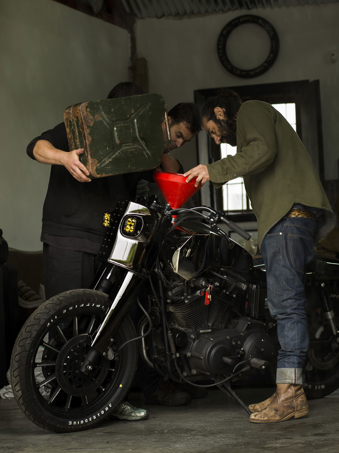 El Solitario's founder  David Borrás  (R), a friend of him (2ndR) and his mechanic Toni (L) fill the Malo/Bueno´s  tank  for the first time at El Solitario workshop garage on April 30, 2015 in Galician Rias Baixas, Spain. Ex commodity trader David Borrás and his wife Valeria Líbano founded  El Solitario Motorcycles  as a personal bet to offer their own  style  of conceiving motorcycles and the fashion market related with them.  Malo/Bueno  is the customization of a 1200cc  Harley Davidson Sportster . Cast sculptors, a community trader and a musician have something in common: they have made the passion of customizing motorbikes their own business. Valtoron Sculptured Motorcycles, Café Racer Obsession and El Solitario Motorcycles are the dreams-come-true of the Delgado Brothers, Federico Ruiz and David Borrás.