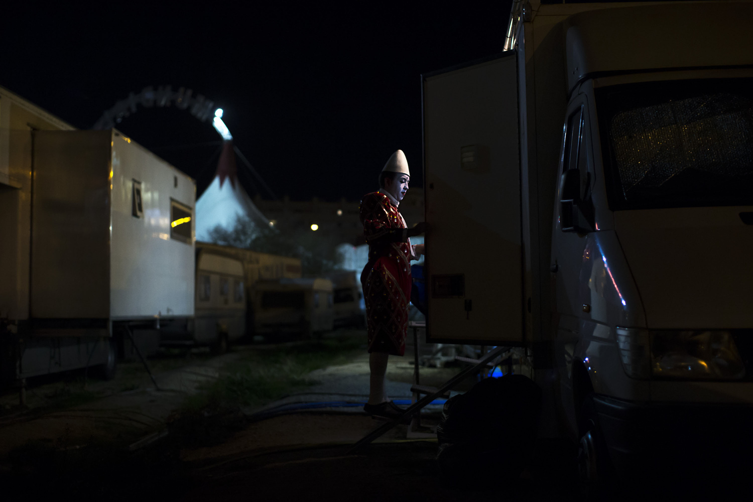 "Clown  Juanjo  Leon  enters to his  caravan-truck  at  Gran Circo Mundial circus' backstage  dressed up as "" Carablanca "" after an evening performance on November 27, 2015 in Madrid, Spain. His brother Dani adapted this truck into the caravan where he lives. The family travels together with this truck pulling their parents' caravan.  Gran Circo Mundial  is a 40 years-old Spanish  circus  where  famil y lifes and stories have mixed together across the time. From the  trapeze  artists of the  Pyongyang National Circus  to the  Rampin  family descendants,  clown s,  magician s or aerial  permormer s share the  stage  and part of their private lifes. Their show was running inMadrid in Autumn 2015."