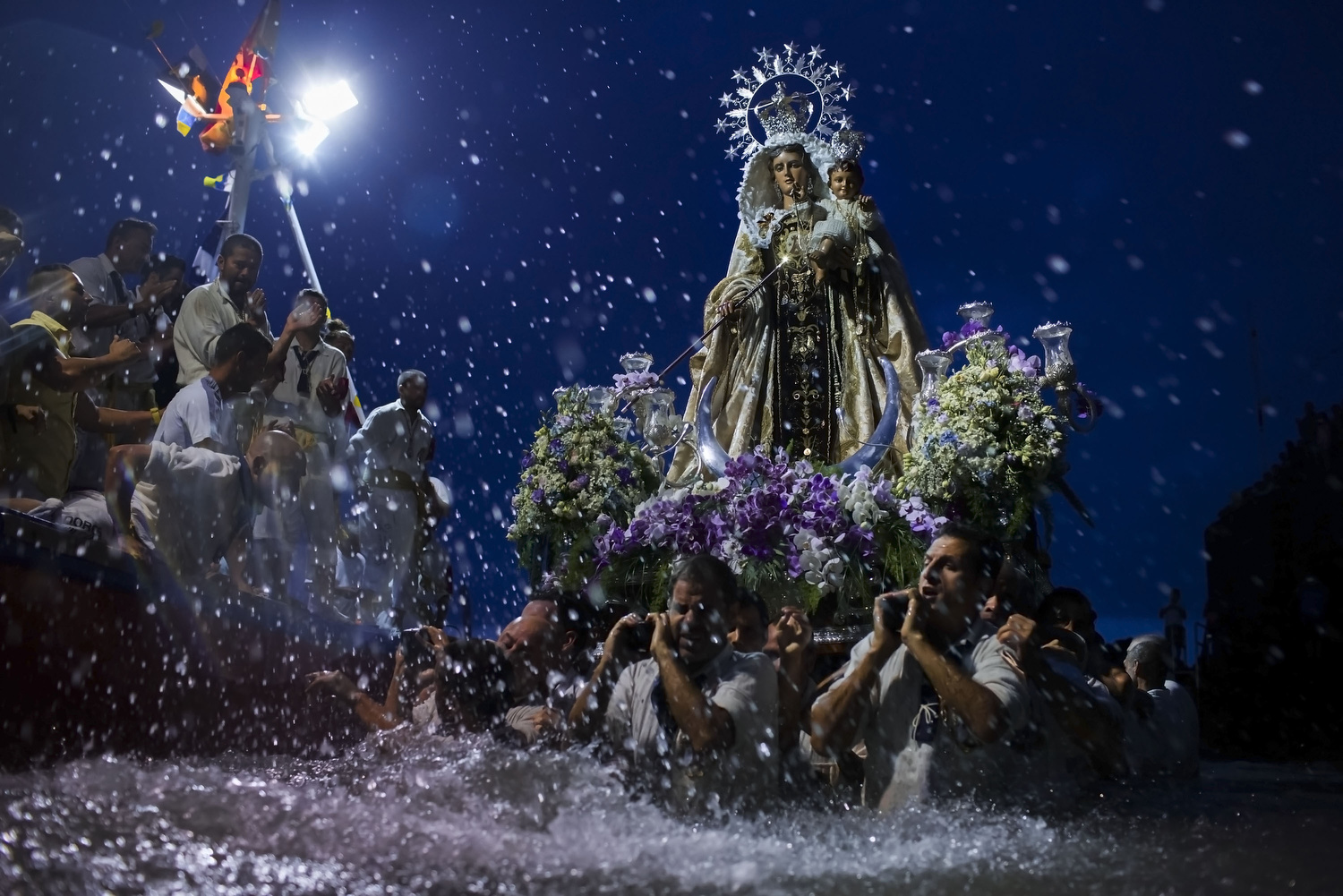 Carriers of the Great God Power  brotherhood  unload  Virgen  del  Carmen   statue  after its journey on July 15, 2014 at  Puerto de la Cruz   dock  on the  Canary island  of  Tenerife , Spain. Since 1921, the statue of the Virgen del Carmen,  patron saint  of  fishermen , has been carried with great fanfare annually as part of July Festivities to the Puerto de la Cruz dock where, at the end of its procession, it is hoisted aboard a decorated  boat . In recent years, attendance at the event has numbered more than 35,000 people.