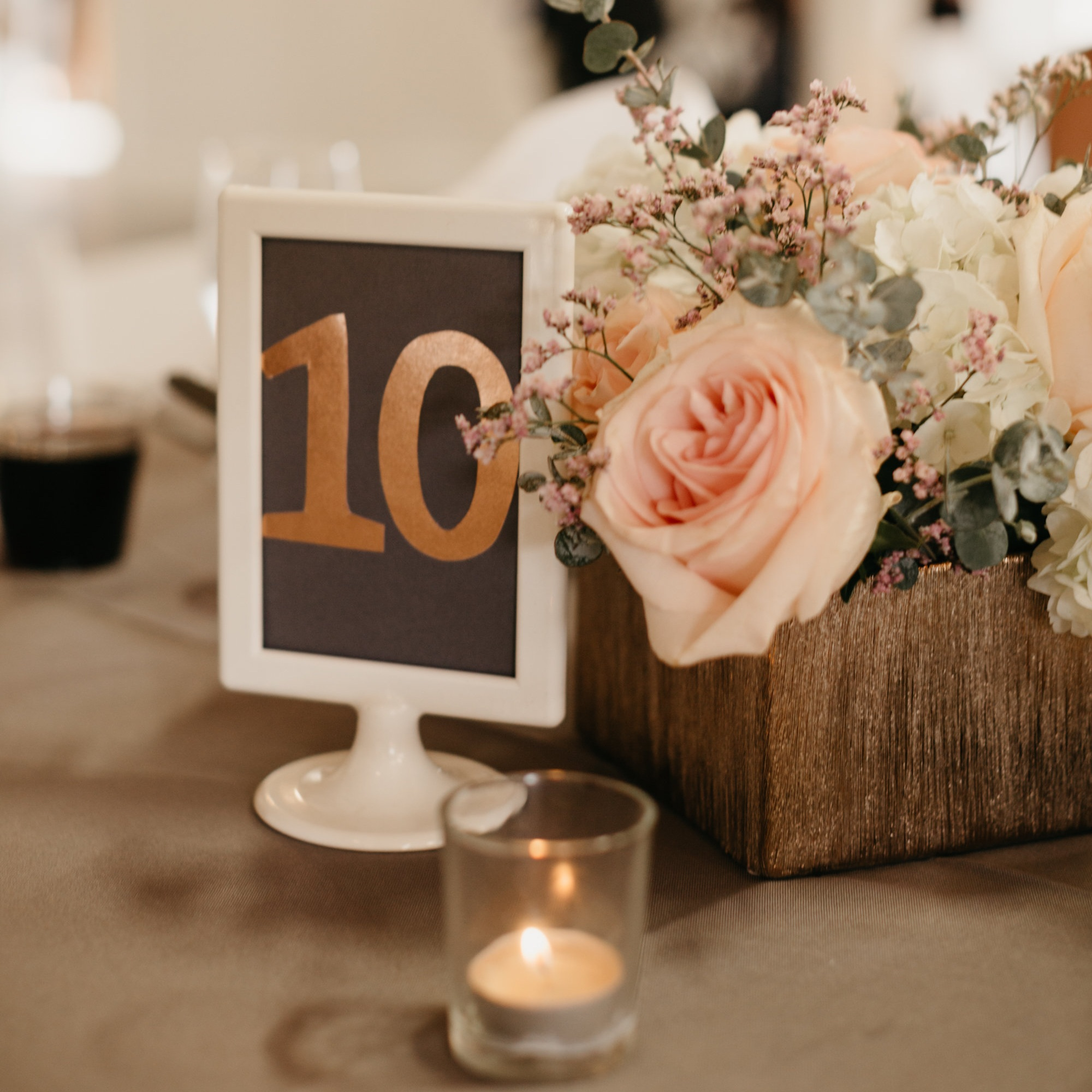 Peach and sage flower bouquet in a wooden planter box with a candle and white-framed table sign at Vista View Events in Colorado