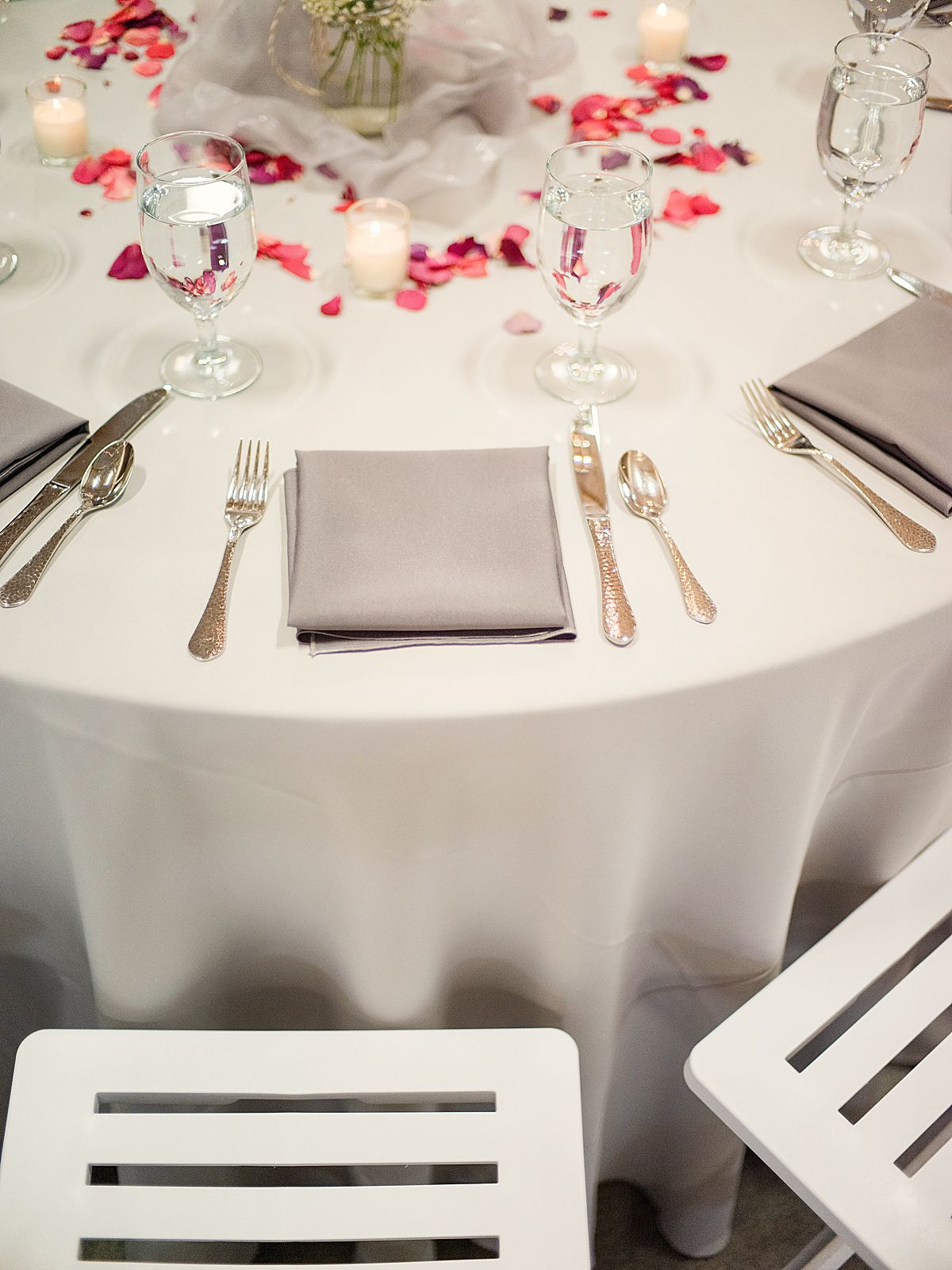 Real glasses and flatware on a round table with a white tablecloth, gray cloth napkins, and rose petals at a mountain wedding venue in Colorado