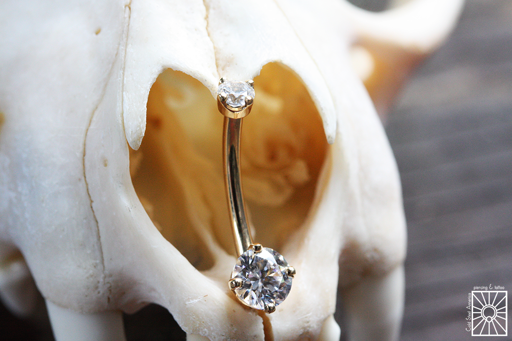 Solid Yellow Gold navel curve featuring prong-set clear cubic zirconias from Body Vision Los Angeles.