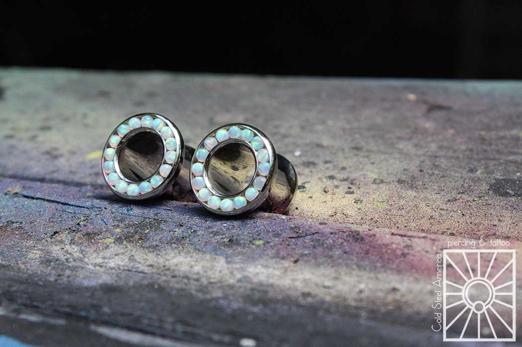 Implant-grade steel and synthetic White OPal gemmed eyelets from Industrial Strength.