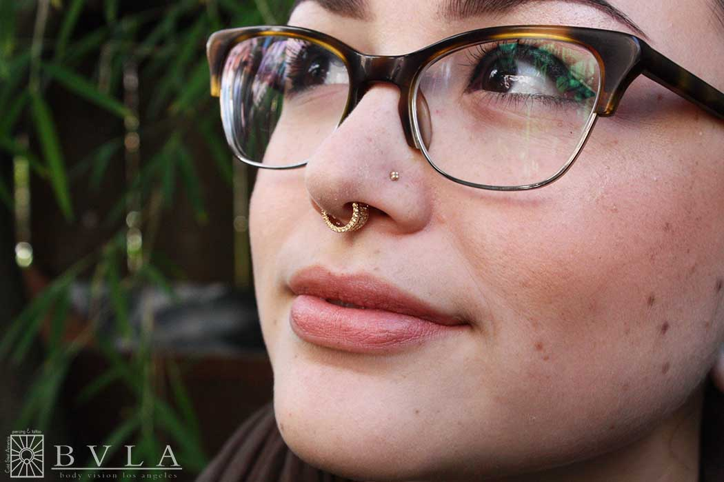 """Look. At. This. Beautiful. Face. Devin is officially the fanciest person on staff.  We posted photos yesterday of her gorgeous new septum piece from Body Vision Los Angeles, and here it is in action! Solid 14 karat Yellow Gold """"Tiara"""" clicker with a whole fistful of Champagne cz's. Just amazing."""