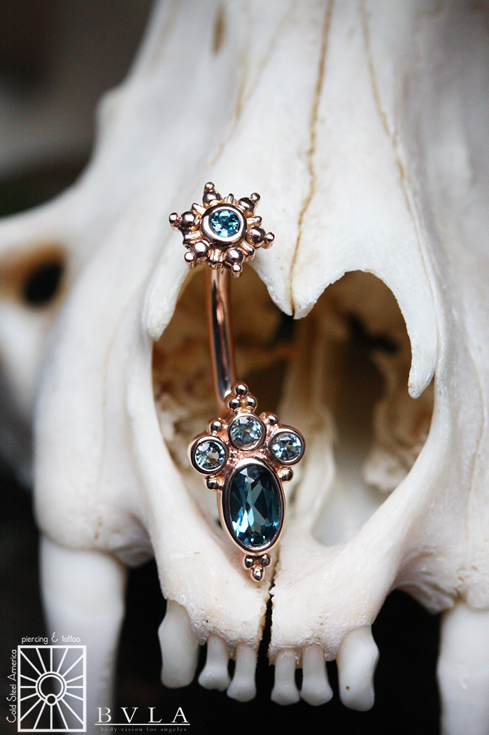 This custom piece from Body Vision Los Angeles is absolutely gorgeous! 14g (1.6mm) solid 14k Rose Gold J-curve featuring genuine AA London Blue Topaz and Aquamarine stones.