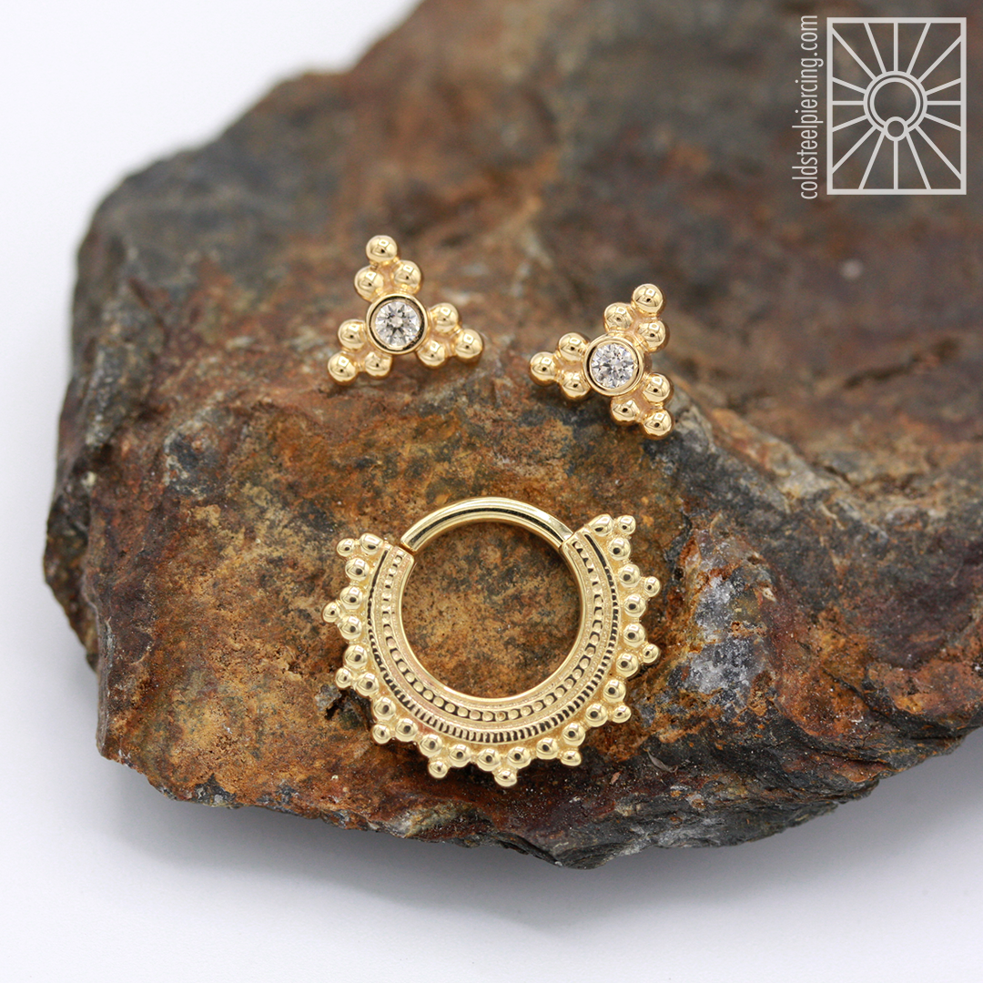 """Solid 18k Yellow Gold and cz """"Sabrina"""" threadless ends from Anatometal, and 14k Yellow Gold """"Afghan"""" continuous ring from Body Vision Los Angeles."""