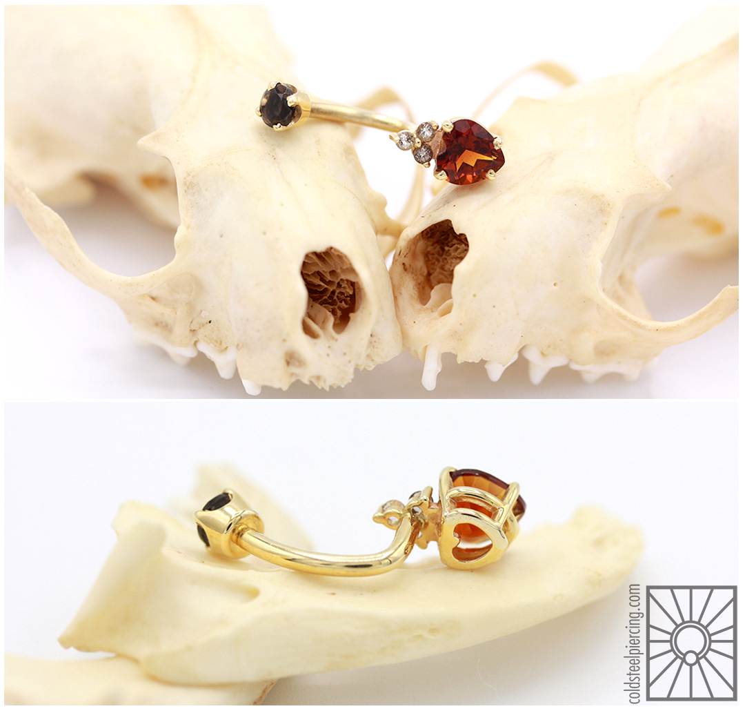 """How has this gorgeous piece not found a home in the handful of years we've had it?! Yellow gold """"Honor"""" j-curve from Body Vision Los Angeles,featuring genuine Citrine and Smokey Quartz stones (and the adorable secret heart cutout on the back 😍)"""