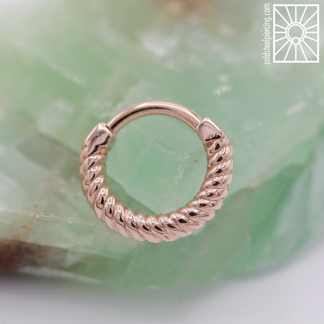 """What a great start to the new year! You folks have been keeping us busy busy busy, but we wanted to grab a second and showcase this gorgeous rose gold """"Desiree"""" hinged ring from Body Vision Los Angeles that we ordered for a wonderful client. This braided baby is going to look so fantastic in her septum piercing!"""