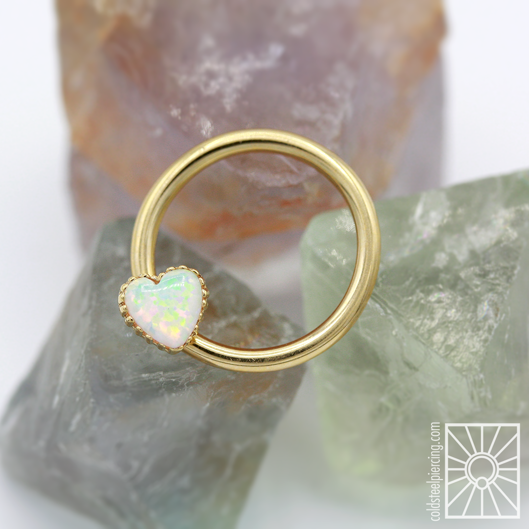 Solid 14k Yellow Gold captive bead ring from Body Vision Los Angeles featuring an 18k Yellow Gold and synthetic White Opal heart from Anatometal.