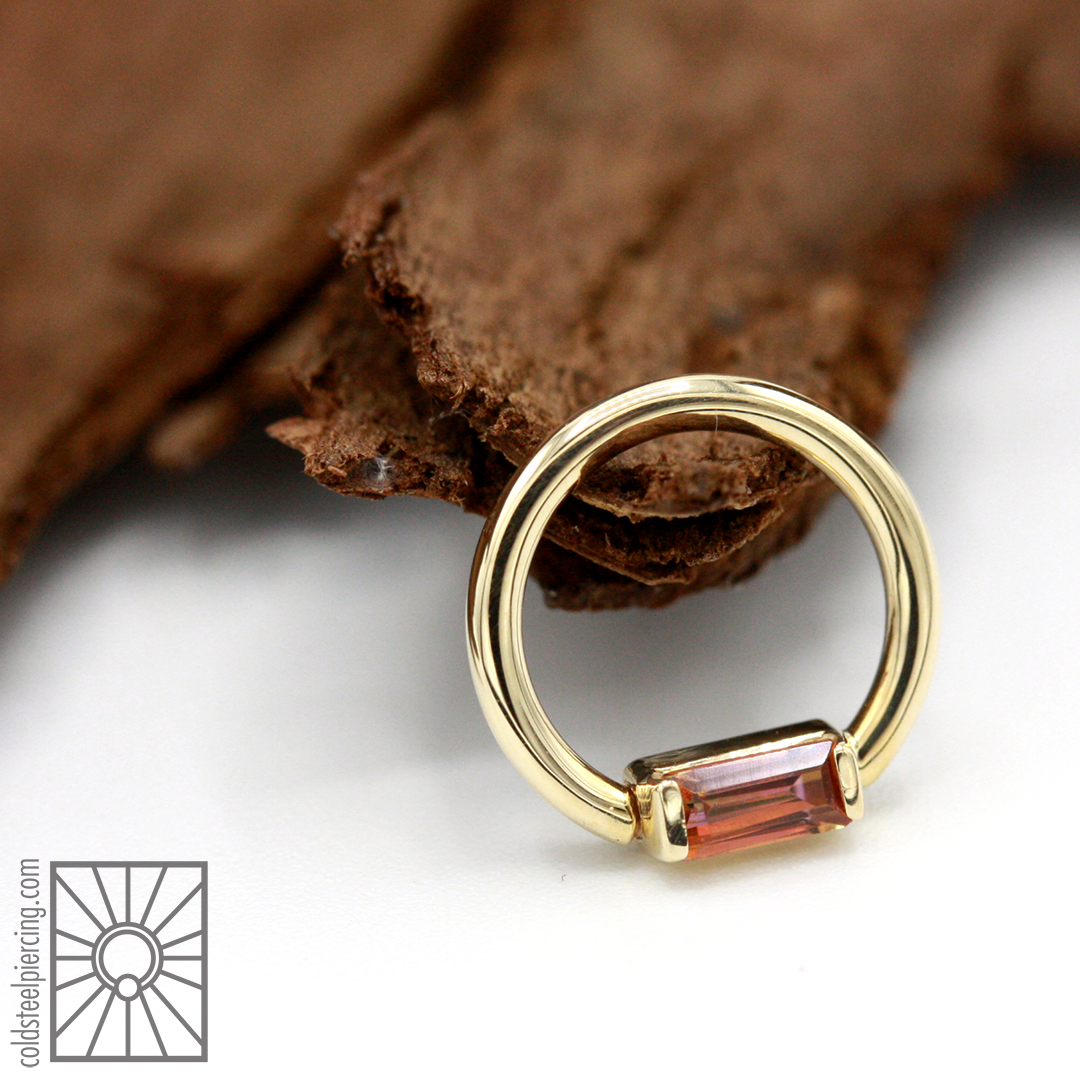 """16g 5/16"""" solid 14k Yellow Gold continuous ring with baguette-cut genuine Anastasia Topaz from Body Vision Los Angeles."""