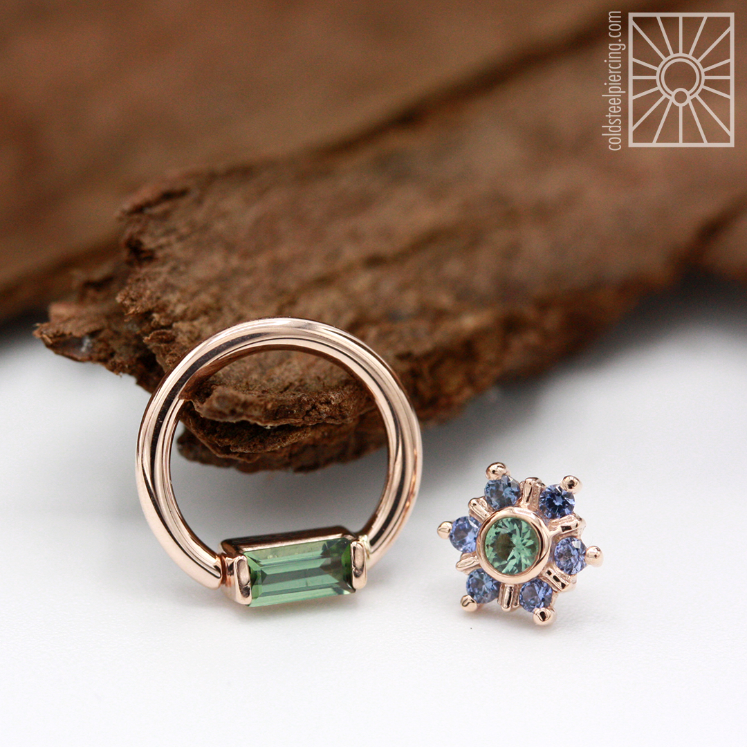 """Now this is a dynamic duo! 16g 5/16"""" solid 14k Rose Gold continuous ring with baguette-cut genuine Seafoam Tourmaline, and a Rose Gold """"Mini Toltec"""" threadless end featuring genuine Polar Sapphires and Seafoam Tourmaline. Both pieces from Body Vision Los Angeles."""