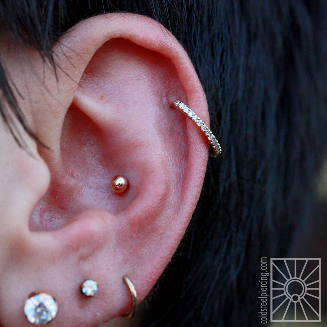 """This wonderful client is building such a great collection of jewelry and we are so excited to add to it! This gorgeous """"Telesto"""" ring from Body Vision Los Angeles we installed in their healed helix piercing (not done by us) is a definite showstopper - 14k yellow gold holding 19 genuine diamonds, how could it not be?!"""
