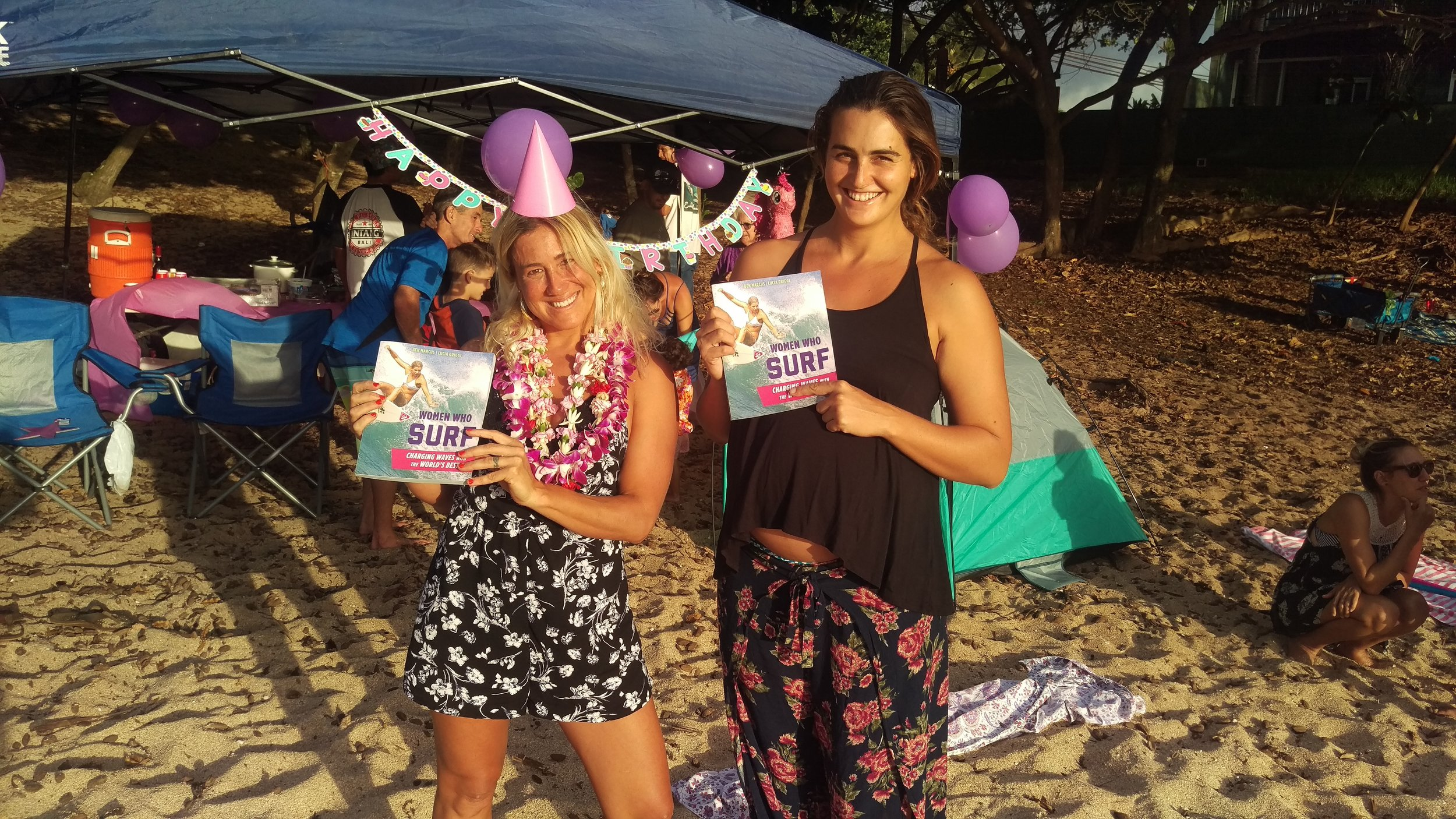 The charming and glamorous Mercedes Maidana and the strikingly tall and  way  pregnant Wrenna Delgado stand with their fresh copies of  Women Who Surf  at Three Tables, North Shore, Oahu. Photo: Ben Marcus