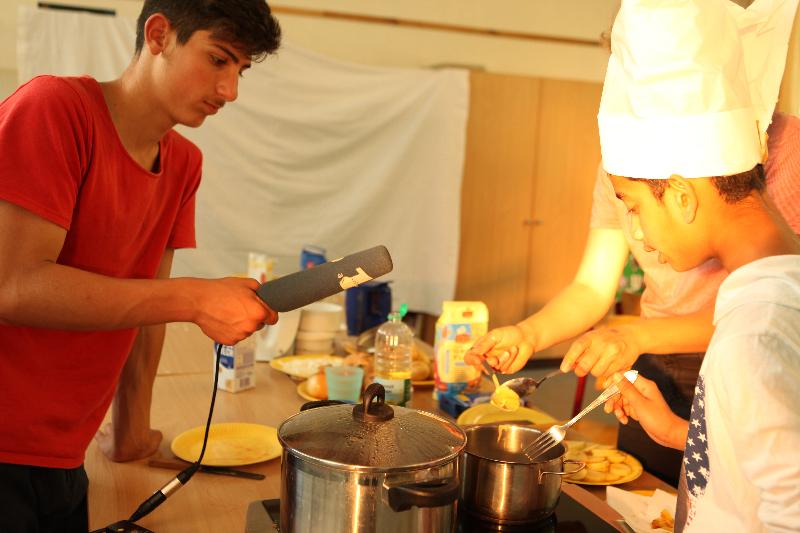 Geflüchtete und nichtgeflüchtete Kinder und Jugendliche inszenieren eine Kochshow über typisch deutsche und syrische Gerichte. Ziel war es, sich gegenseitig das Essen näher zu bringen und sich mit kulturellen Unterschieden und Gemeinsamkeiten auseinanderzusetzen.