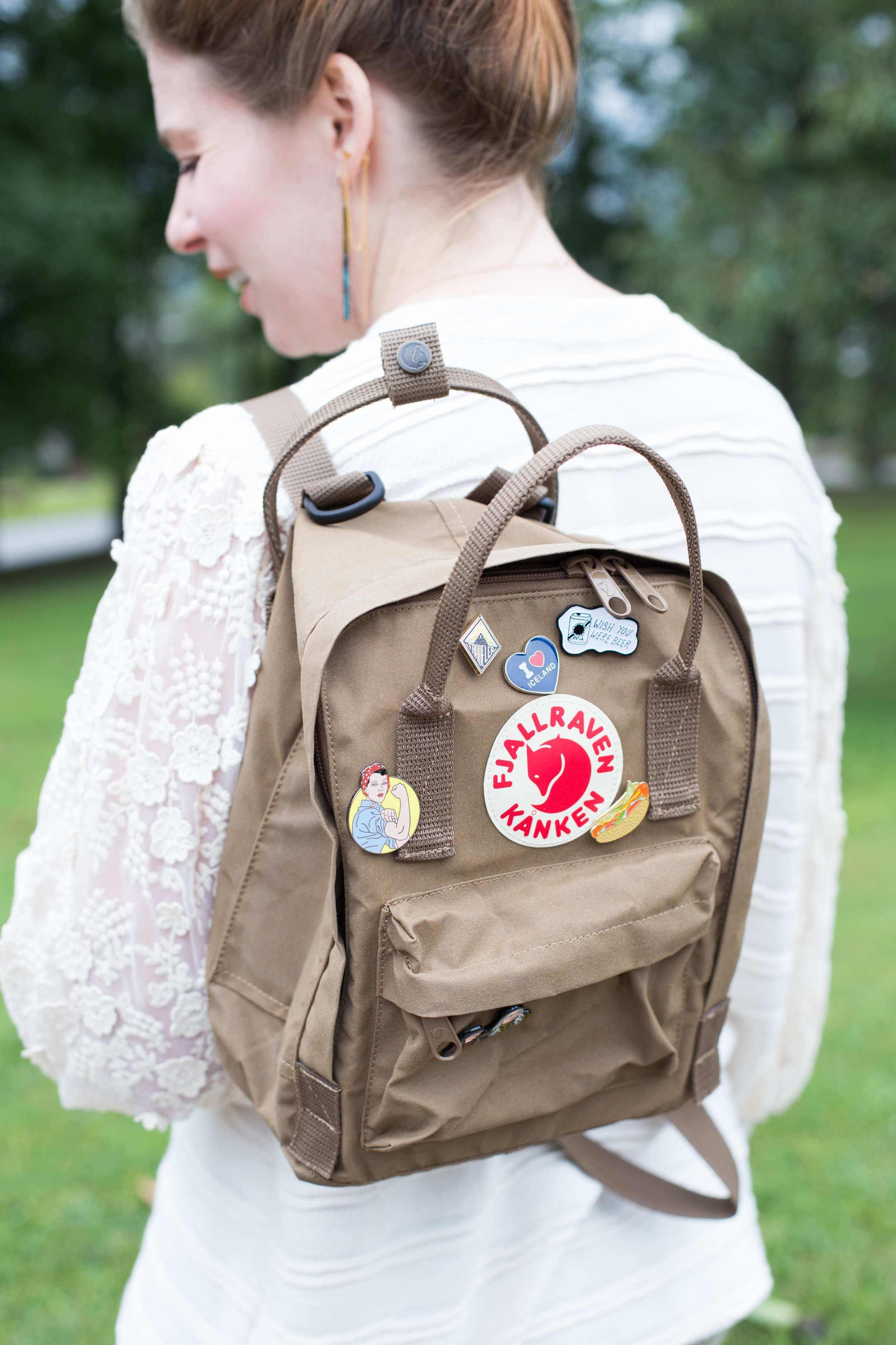 Fjallraven Kanken mini backpack covered in enamel pins.