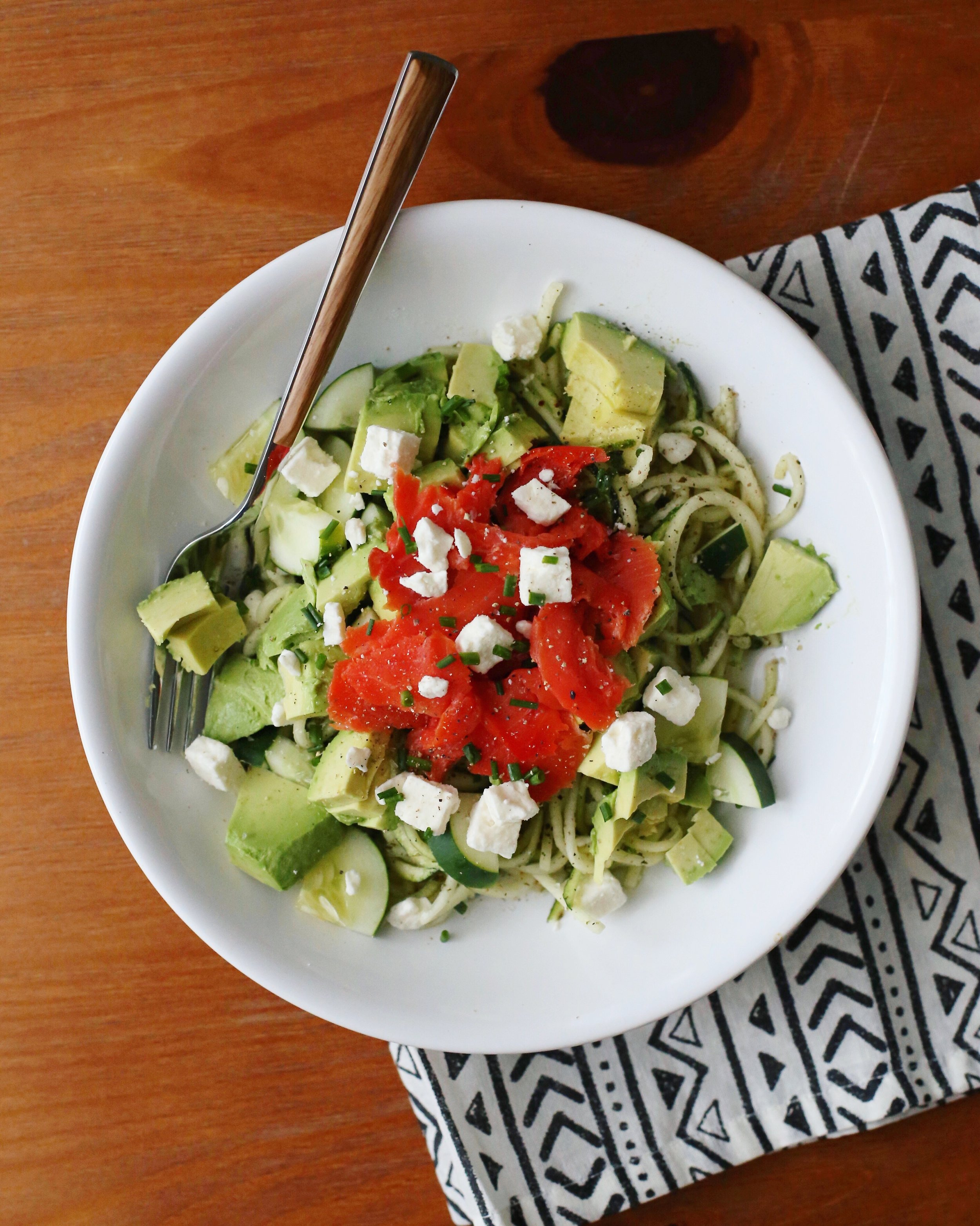 Summer salad with cucumber, avocado, zucchini, feta cheese, and smoked salmon drizzled with a light lemon and olive oil dressing.