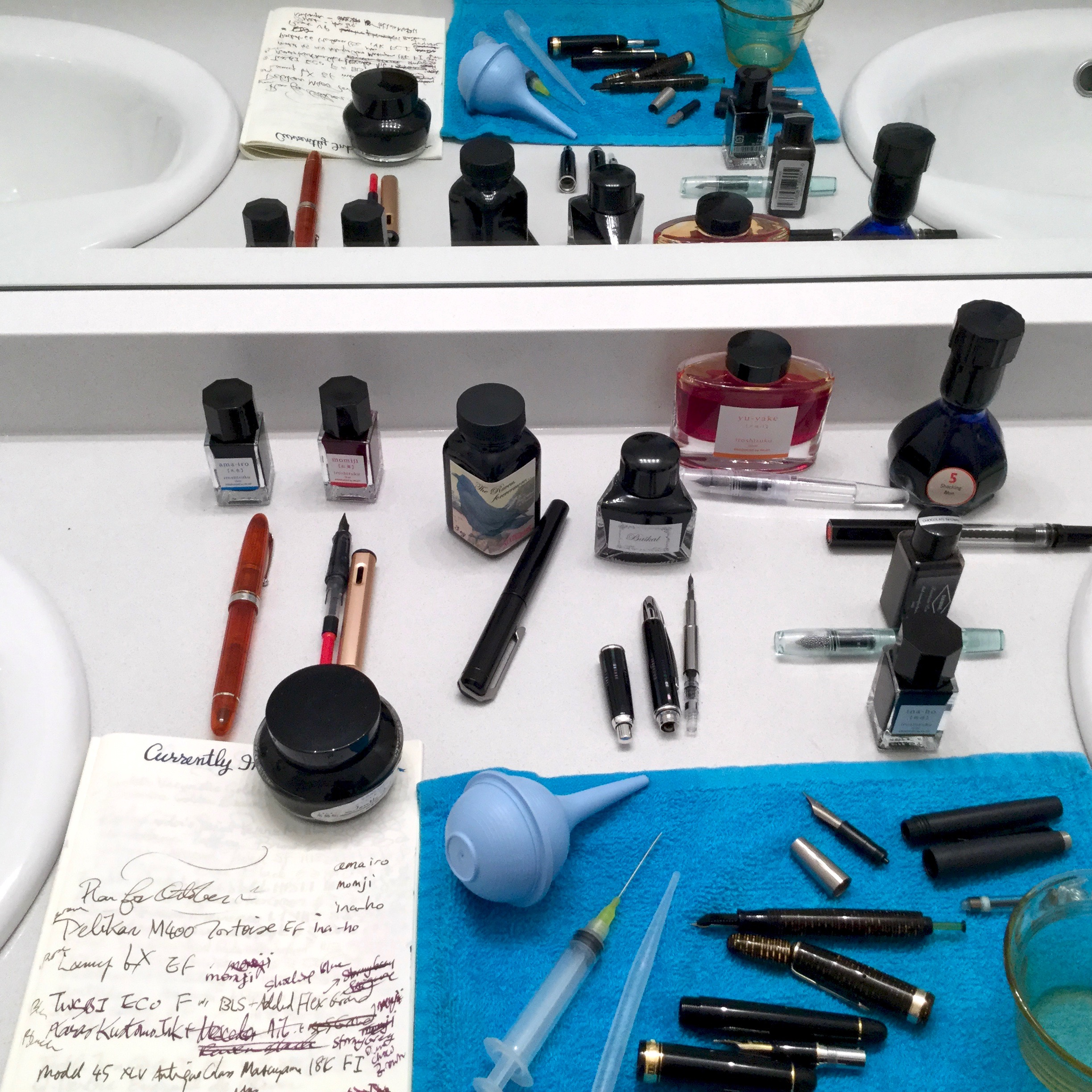 In foreground & mirror reflection, on top of blue towel: bulb syringe, blunt tip needle, cleaned and sorted pen parts