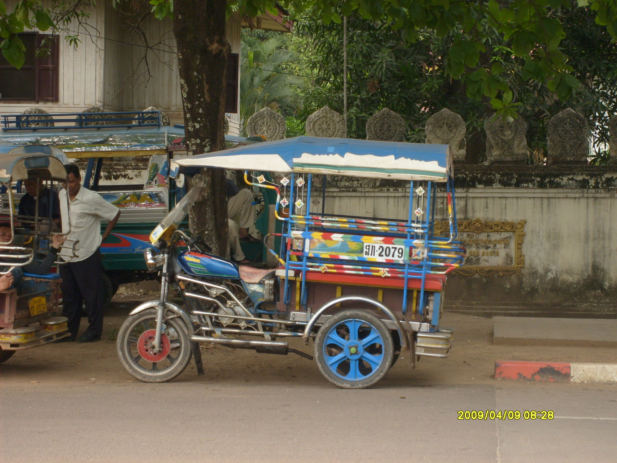 This is a tuk-tuk. These three-wheeled contraptions act as family vehicles, taxis, and schoolbuses.