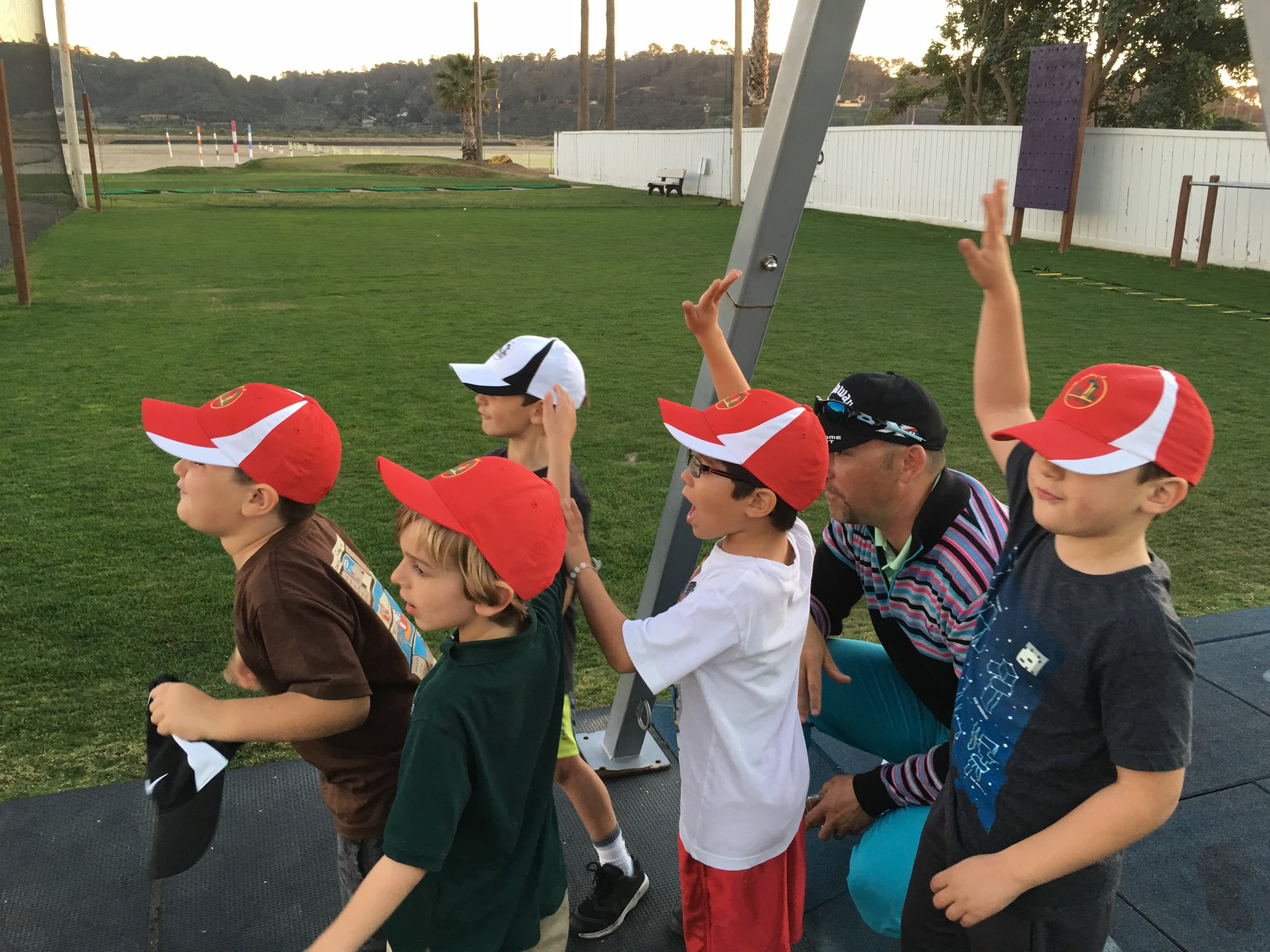 Young athletes proudly sporting the hats they earned for their golf prowess.