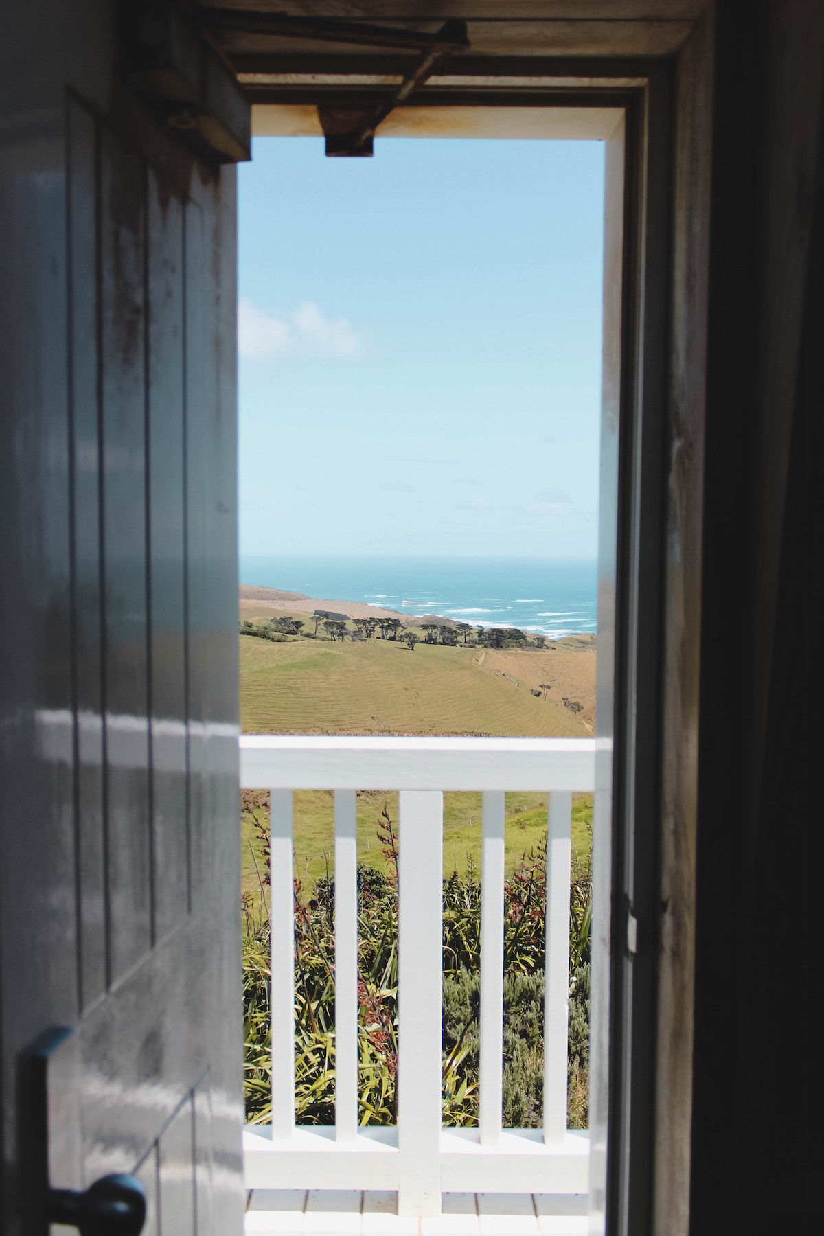 A door opening to a porch with a white railing, overlooking a hill and blue water