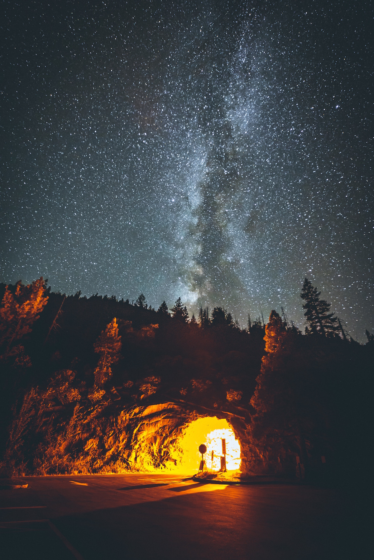 Night sky over a mountain with a lighted tunnel running through it