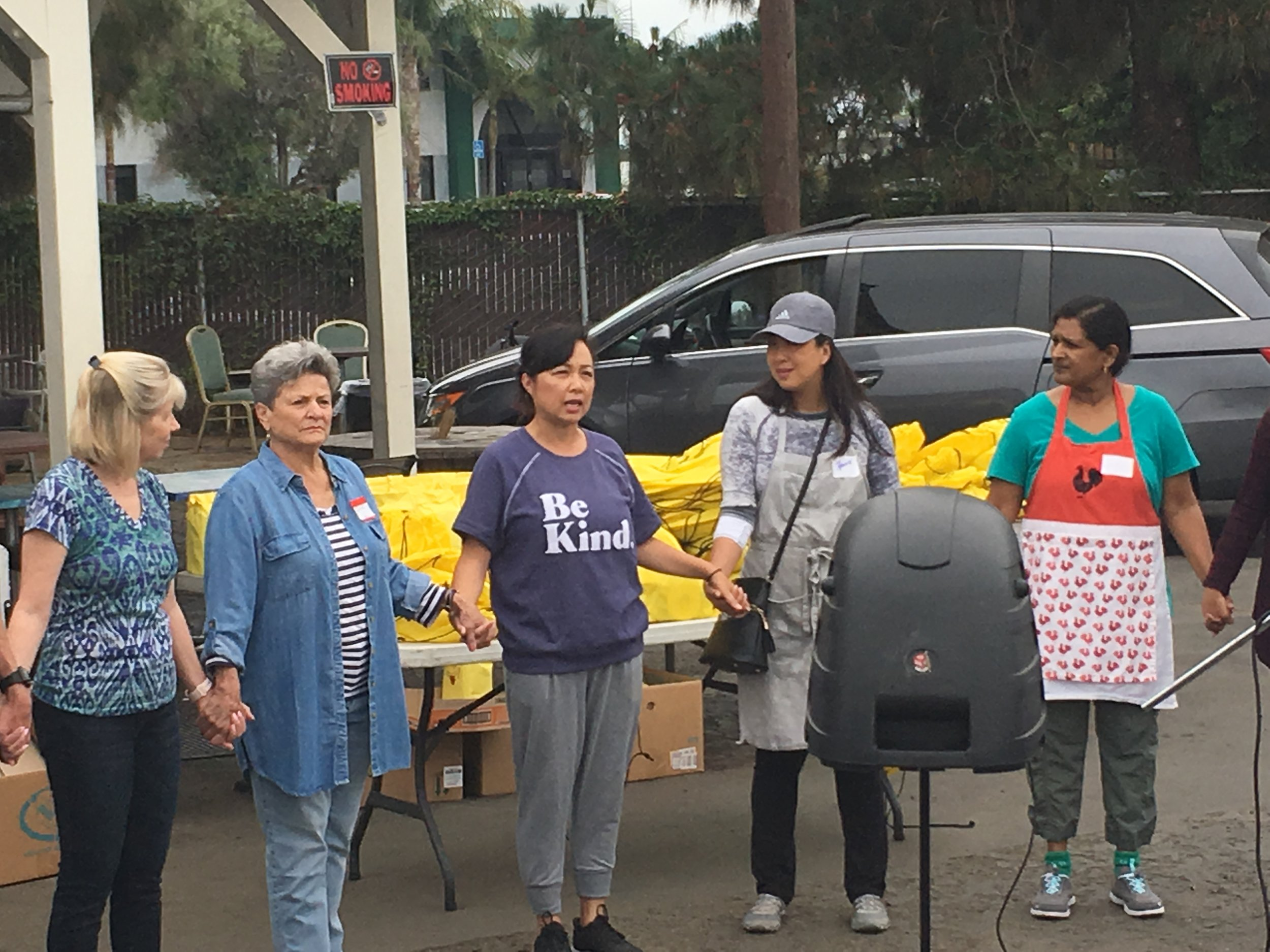 Jennifer Norseen (wearing the cap) and other volunteers gather to pray as they serve at Mary's Kitchen, filling bags with emergency food and personal toiletries provided by Operation Be Kind.