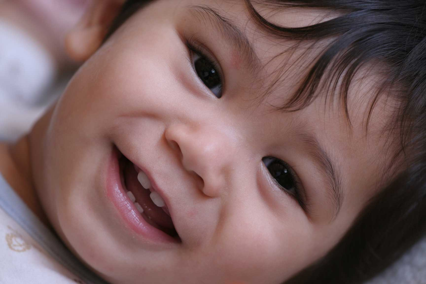 infant smiling and showing 4 baby teeth