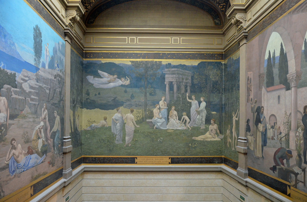"""Sacred Wood Dear to the Arts and Muses"" by Pierre Puvis de Chavannes   Permanently installed oil on canvas, 1884 (approx. 16x20 ft). One of three large murals in the stairway, Palais de Beaux Arts, Lyon, France. Pierre Puvis de Chavannes, 1824-1898.  Puvis de Chavannes was one of the most prolific of the government supported painters of the Second Empire and the Third Republic, even obtaining one of the most prestigious mural commissions in the United States, for the grand staircase of the Boston Public Library.  Puvis de Chavannes' work is seen as symbolist in nature, even though he studied with some of the romanticists, and he is credited with influencing an entire generation of painters and sculptors, particularly the works of the Modernists. He uses classically-inspired allegorical themes which invoke a timeless past and Renaissance ideals. Yet, he stylistically collapses space and sometimes thwarts those Renaissance ""rules"", giving his work a modern look."