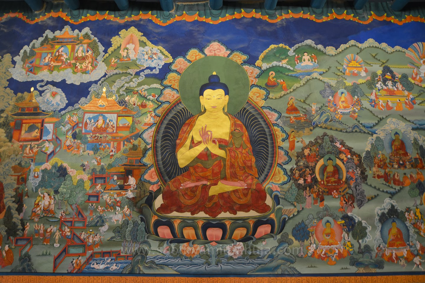 "This beautiful mural is in the Buddhist Monastery Hemis, in Ladakh (""land of high passes"") , a region in the Indian state of Jammu and Kashmir . The technique is most likely ""Fresco Secco"" (Fresco-secco is a wall painting technique where pigments mixed with an organic binder and/or lime are applied onto a dry plaster. The paints used can be casein paint, tempera, oil paint, silicate mineral paint.) They also would be painted on cloth and hung over a wall. The care and attention to detail is remarkable, as well as the exquisite colors. Murals not only honor the Buddhist teachings, they assist in communicating ideas, concepts and stories. It's interesting to compare a Buddhist mural to one of the Italian Renaissance. The Buddhist artists have no interest in imitating ""real"" 3D space. With a spiritual point of view that all time happens at once, then it makes sense. There are thousands of murals in all of the monasteries from northern India through Tibet, Nepal and into China and Korea. Many have survived for centuries in the dry climate of the Himalayas.  Image courtesy of Amit Pahuja's Travelogues"
