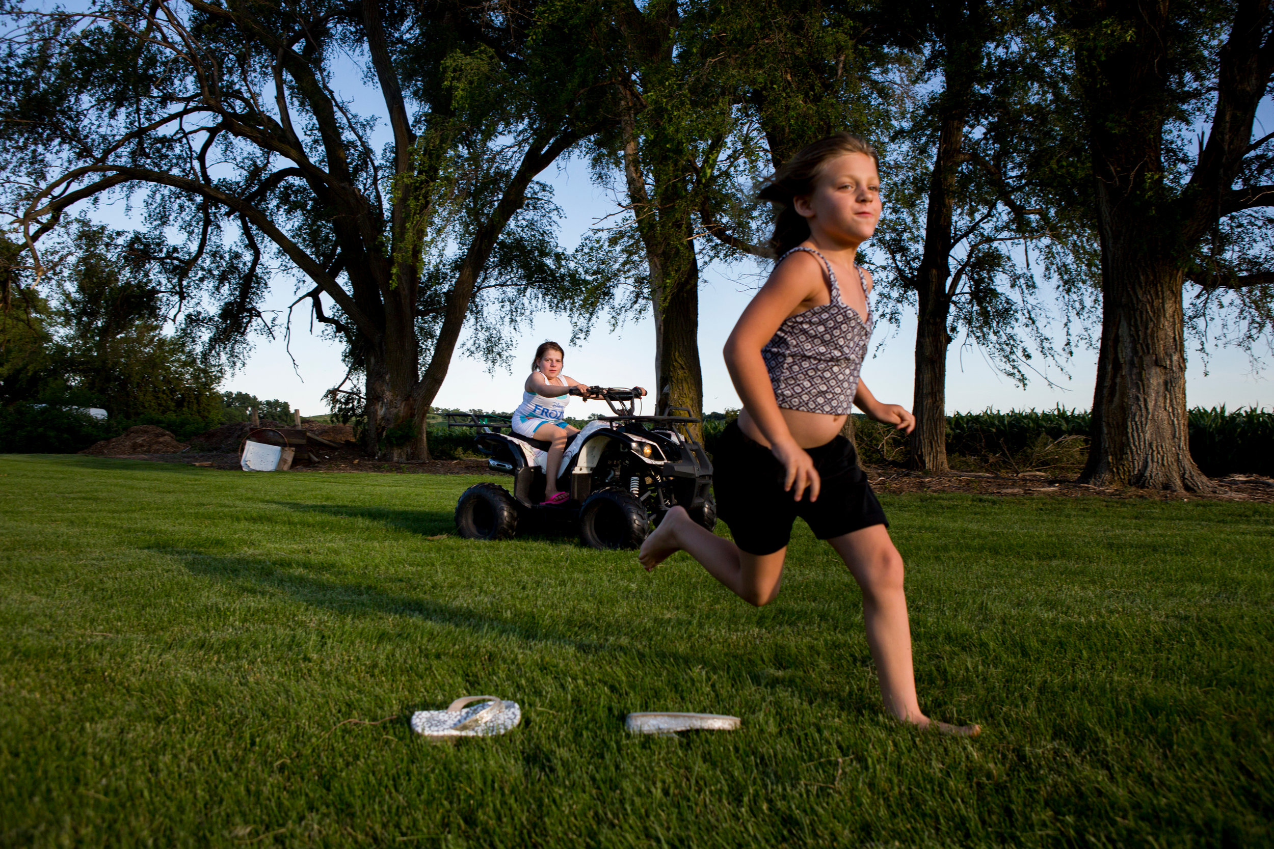 Emily rides on her four-wheeler while playing in the yard with Taylor-Jo. (Kristina Barker for Cosmopolitan)