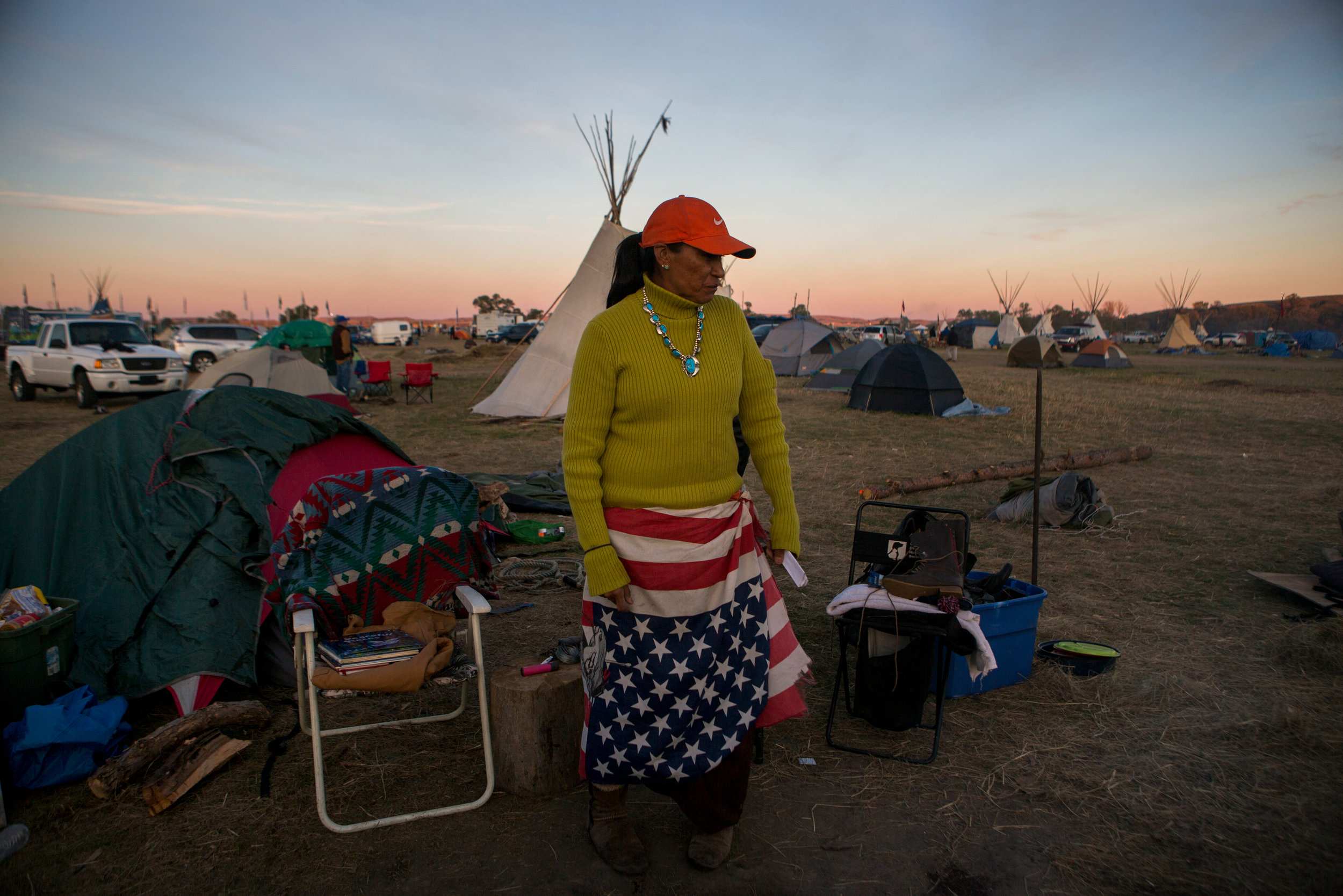 """Stacey Alkire, of Standing Rock Sioux Tribe, currently living in Denver, has been at the Seven Councils Camp for five weeks. Alkire said she was compelled to support her relatives at the camp """"because I'm tired of the govermenting screwing the Natives. They don't create balance with us."""" She continues, """"All we want them to do is honor our treaties. I know this is a poverty-stricken place. But this is a beautiful place. We've never been honored. We've never been respected."""" Saturday marked the 60th day of protest encampments surrounding the Dakota Access Pipeline near Cannon Ball, North Dakota. Law enforcement has reached out to federal agencies for both monetary and personnel assistance. Tensions have flared in recent weeks between law enforcement and protestors, as well as between private security and protestors. Kristina Barker for The New York Times"""