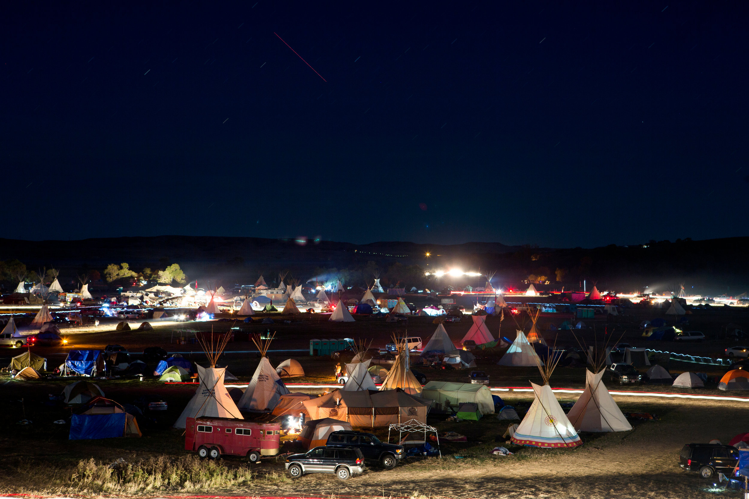 A long exposure shows the movement of activity at the Seven Councils Camp just after dusk on Saturday evening, Oct. 8, 2016. Saturday marked the 60th day of protest encampments surrounding the Dakota Access Pipeline near Cannon Ball, North Dakota. Law enforcement has reached out to federal agencies for both monetary and personnel assistance. Tensions have flared in recent weeks between law enforcement and protestors, as well as between private security and protestors. Kristina Barker for The New York Times
