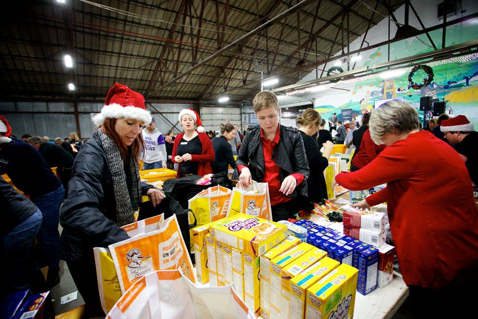 Volunteers assemble food packages for the Moisson Montréal holiday drive. Image  via Facebook.