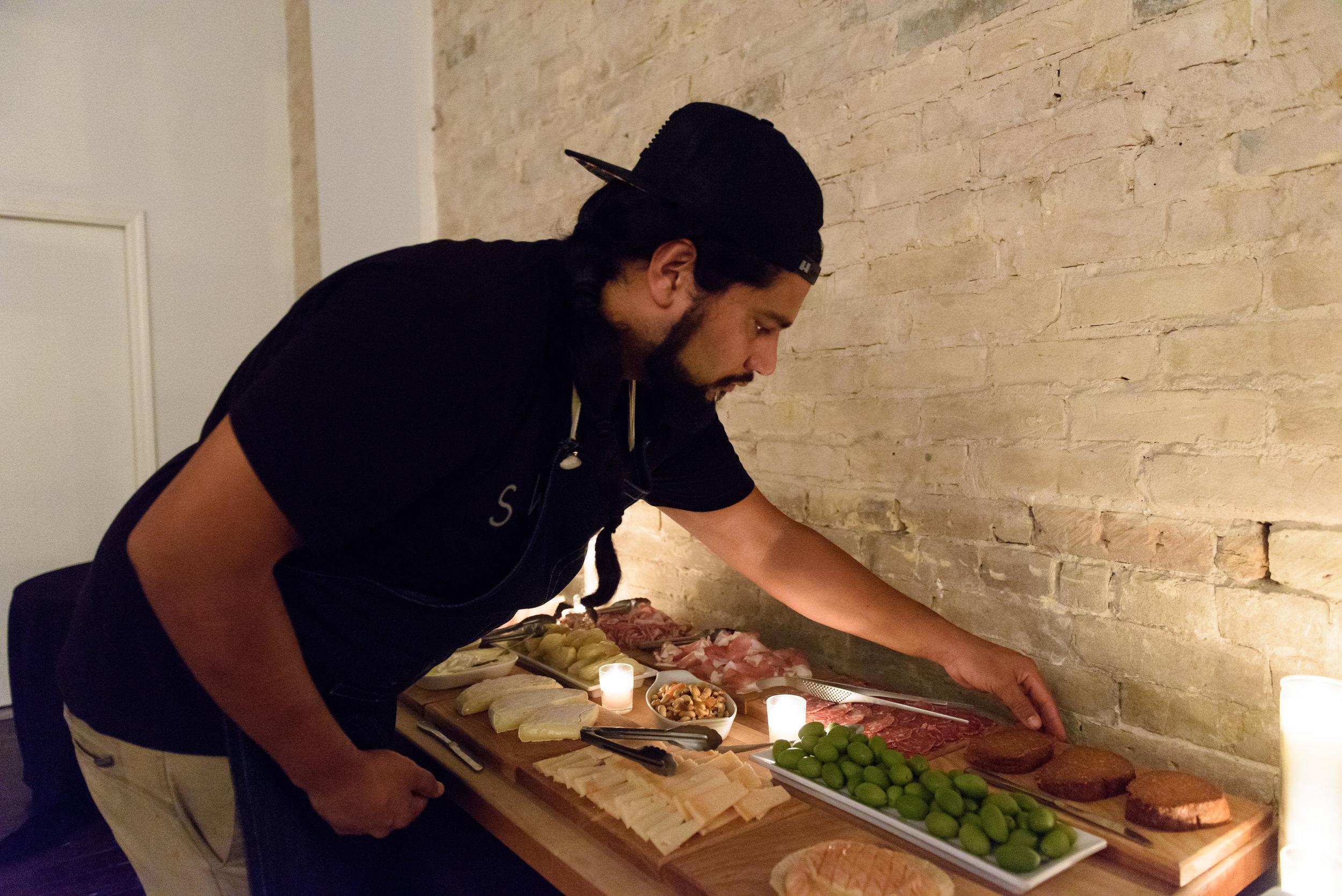 Chef Joe Saenz prepares a charcuterie spread for a recent Saint City Supper Club event. Photo by Louie Preciado.