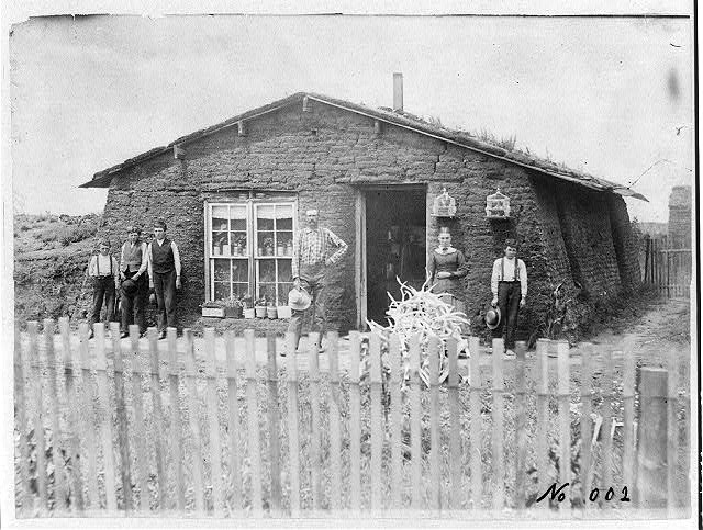 Homesteaders in front of a sod house, 1886. Photo via National Archives.