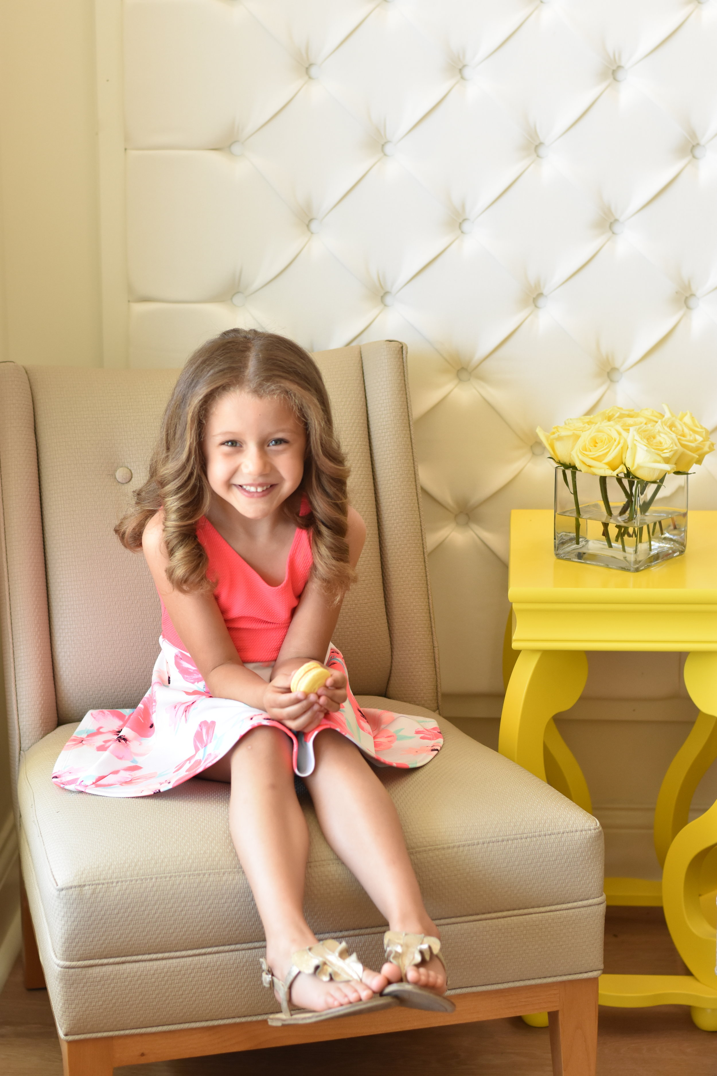 Image of little girl sitting in a chair at DryBar salon after a blowout hairstyle.