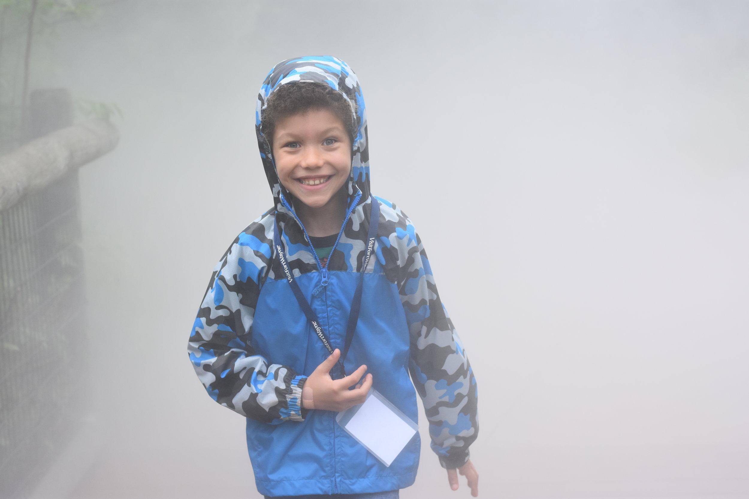 Boy running through the mist at the Fort Wayne Children's Zoo